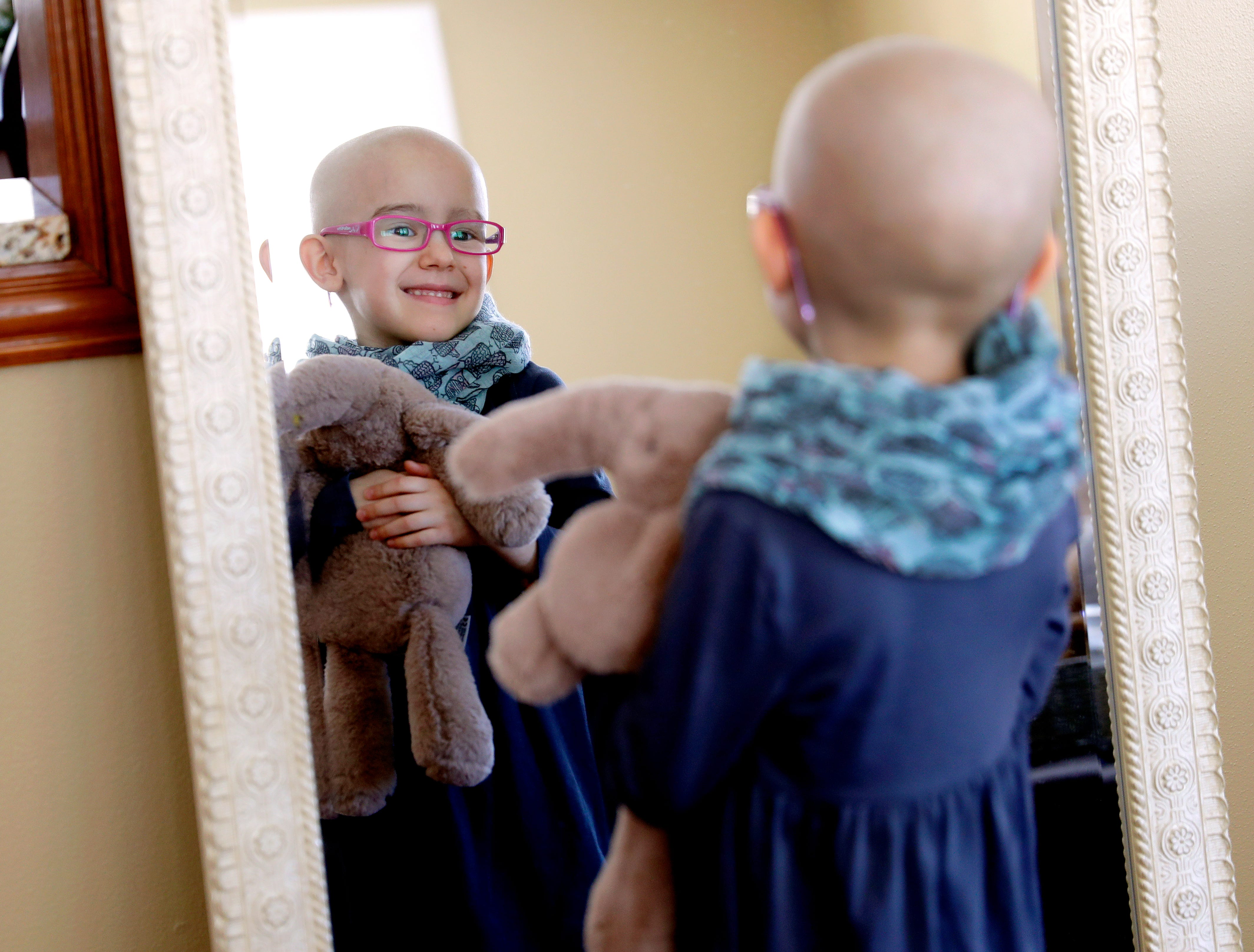 Lily Wertel, 6, smiles in a mirror at her family's home in Wrightstown, Wis. with her stuffed elephant, Toby. A benefit for Lily, who has cancer, is scheduled for May 19, 2019, at the Riverside Ballroom in Green Bay, Wis.