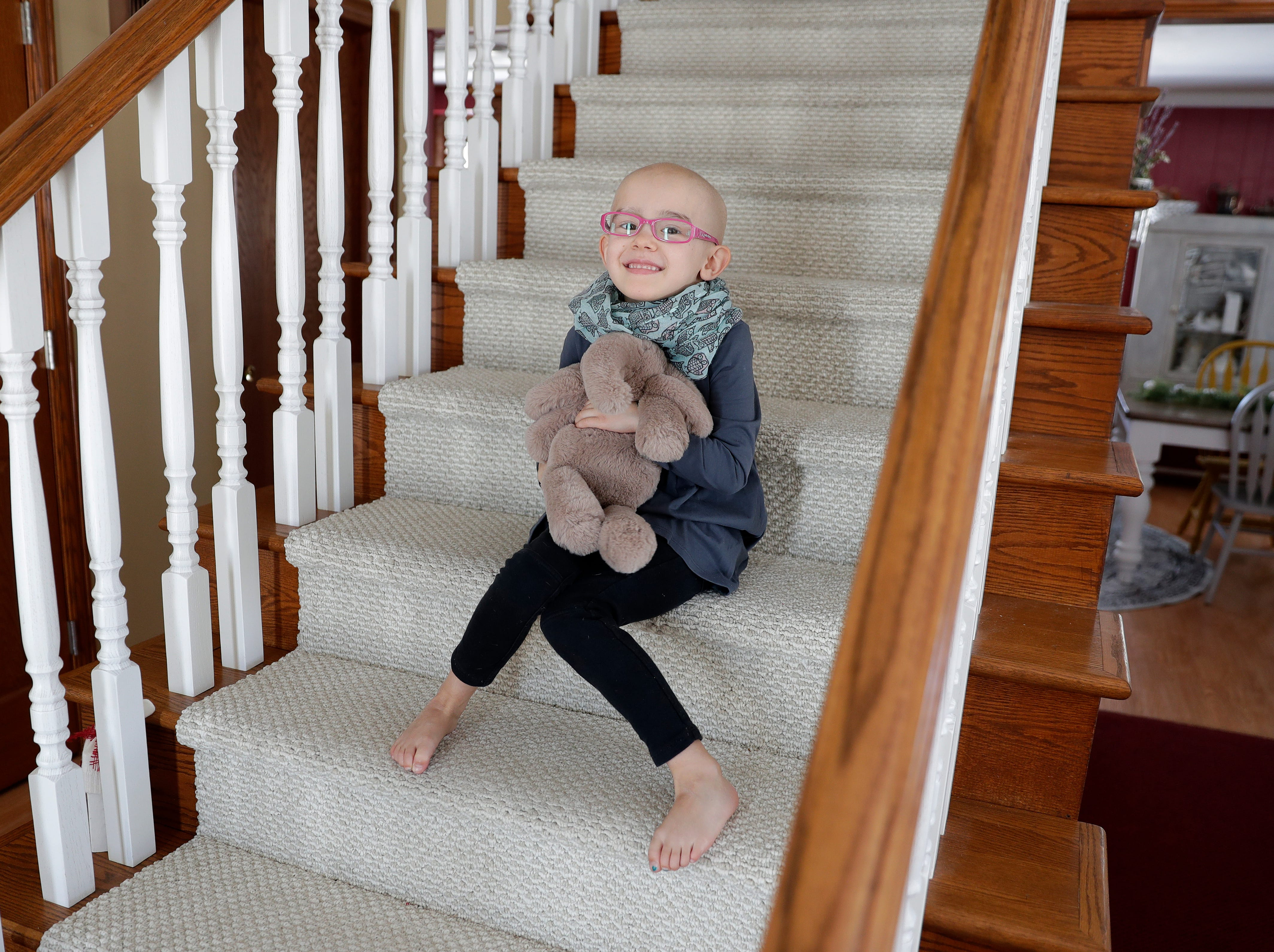 Lily Wertel, 6, sits on the staircase of her family's home in Wrightstown, Wis. with her stuffed elephant, Toby. A benefit for Lily, who has cancer, is scheduled for May 19, 2019, at the Riverside Ballroom in Green Bay, Wis.