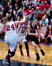 Gillett's Aubrey DeBauch drives the baseline against the defense of Kaelyn Schlies (12) and Natalie Schroeder (24) of Wausaukee, in the first half of the sectional semifinals held in Crivitz on Feb. 28.