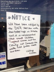 A notice of high nitrate in the water was posted on the door of the Village Kitchen restaurant in Casco, Wis., in April 2017. Contamination in drinking water wells in the regions has been tied to animal waste from farms.
