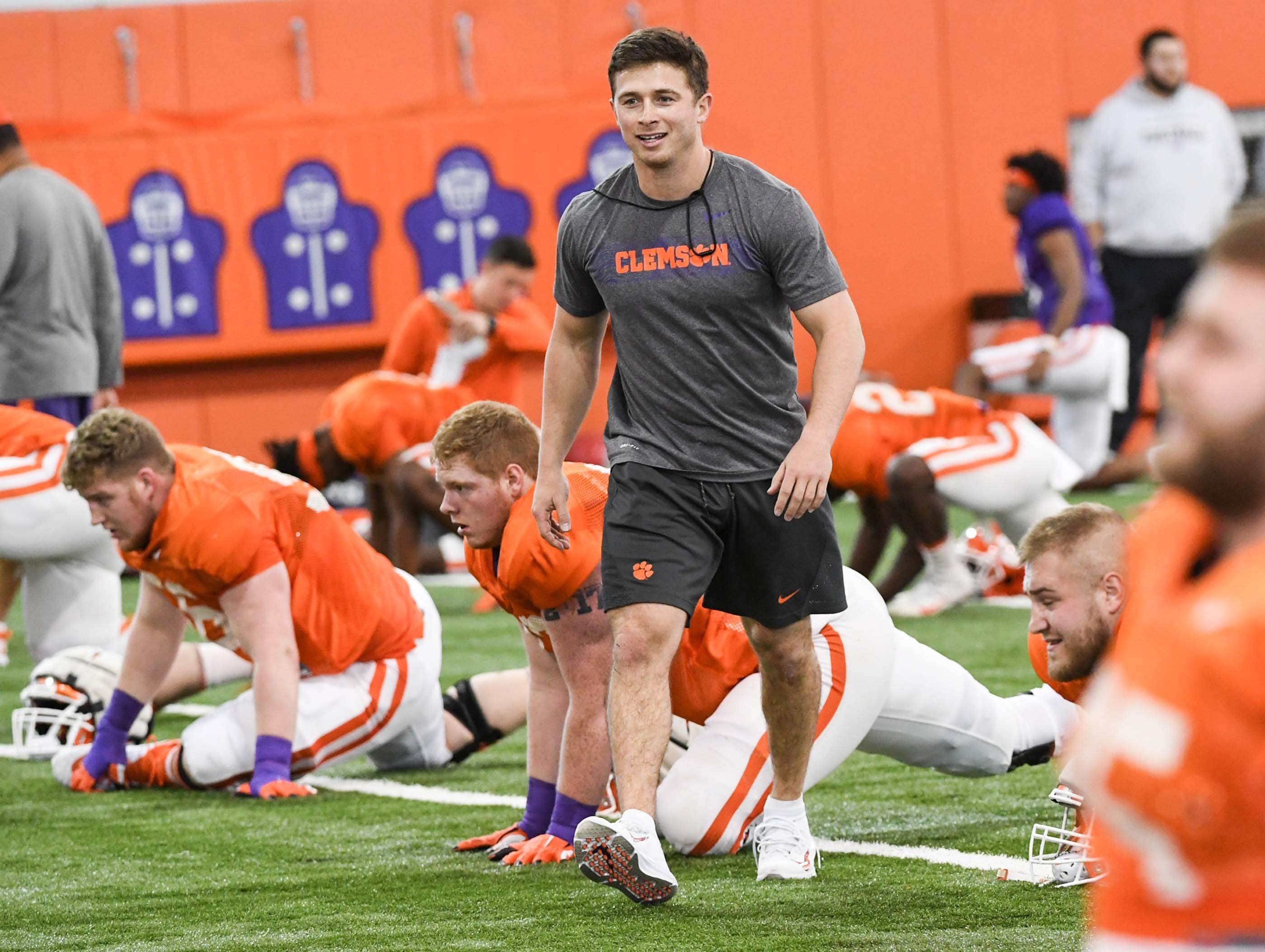 Former Clemson wide receiver Adrien Dunn walks through players stretching during practice at the Poe Indoor Facility in Clemson Monday.