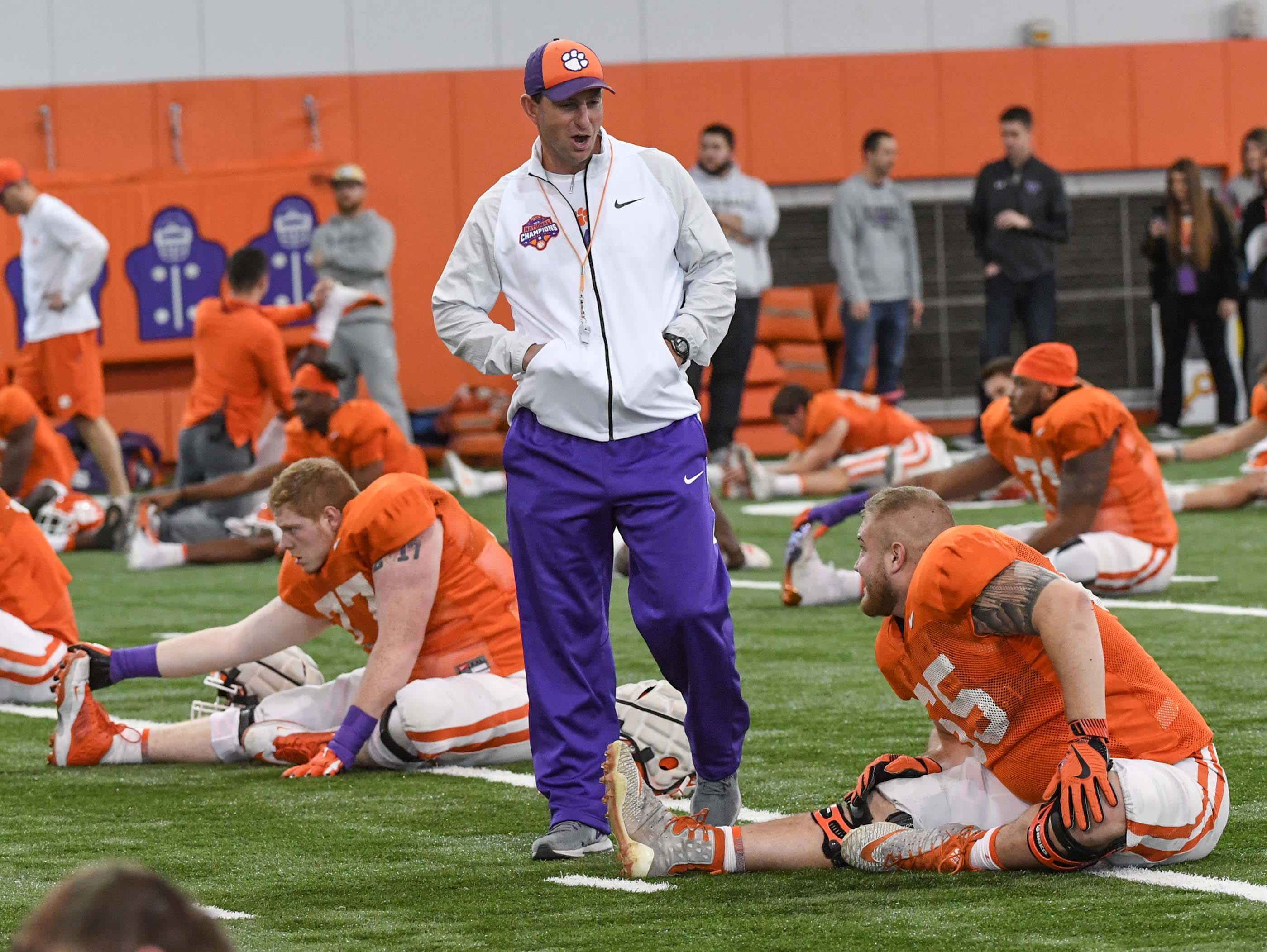 Clemson Head Coach Dabo Swinney walks by offensive lineman Matt Bockhorst (65) and others stretching during practice at the Poe Indoor Facility in Clemson Monday.