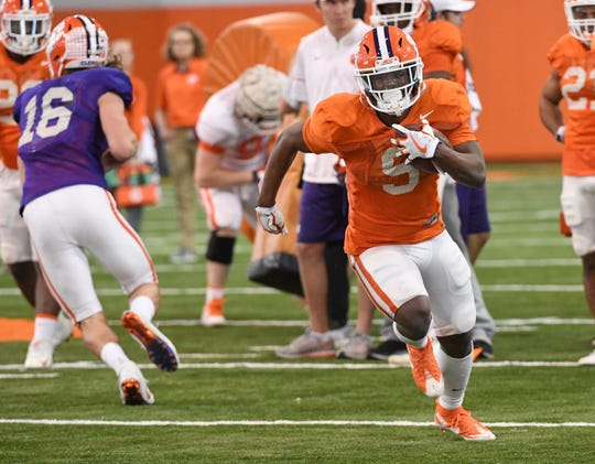 Clemson running back Travis Etienne (9) runs during practice at the Poe Indoor Facility in Clemson Monday.