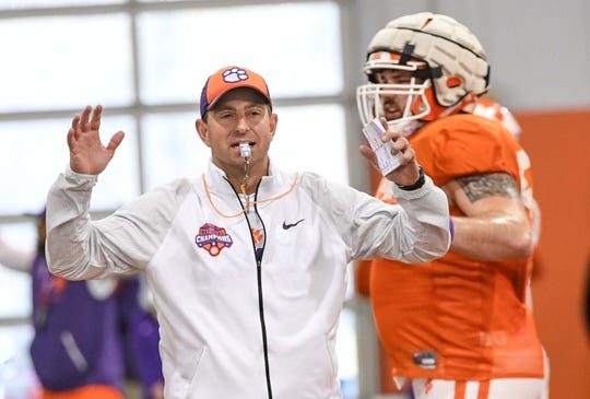 Clemson Head Coach Dabo Swinney and offensive lineman Gage Cervenka (59) do Tiger Jacks during practice at the Poe Indoor Facility in Clemson Monday.