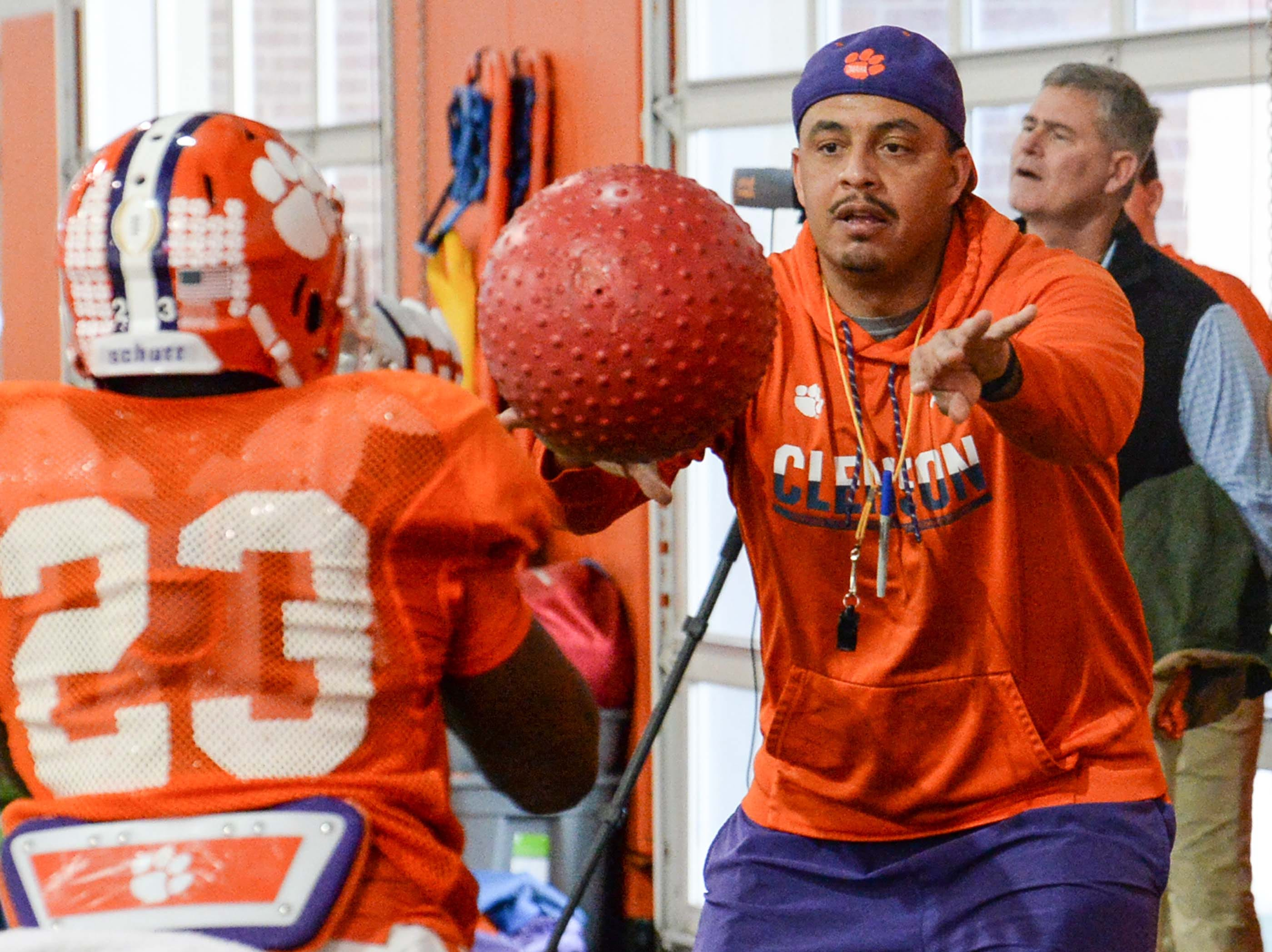 Clemson co-offensive coordinator Tony Elliott passes a ball to running back Lyn-J Dixon (23) during practice at the Poe Indoor Facility in Clemson Monday.