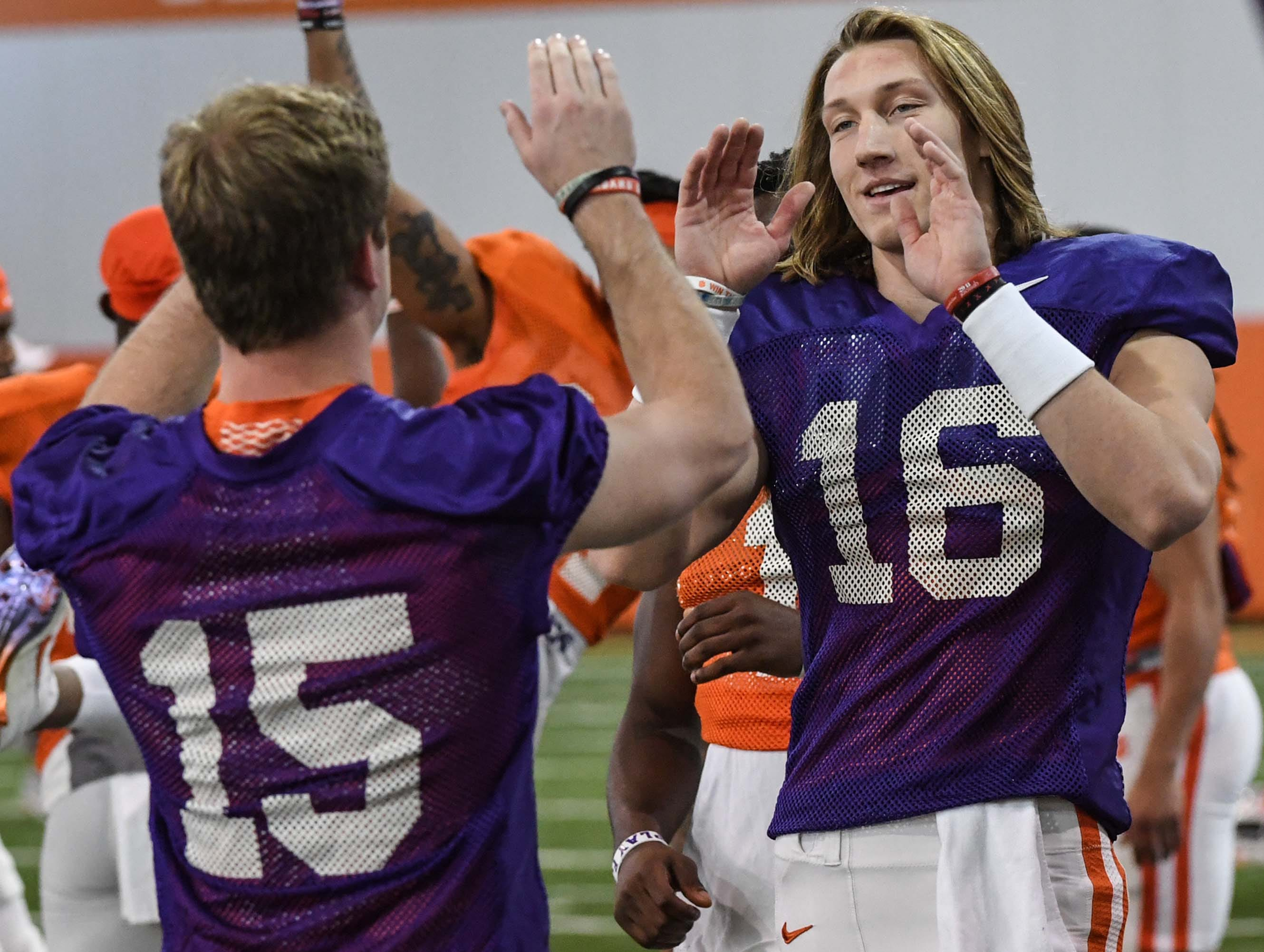 Clemson quarterback Patrick McClure (15), greets quarterback Trevor Lawrence (16) during practice at the Poe Indoor Facility in Clemson Monday.