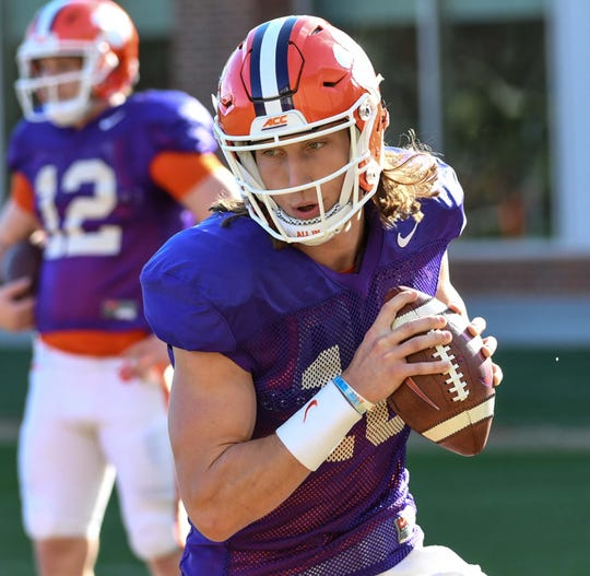 Clemson quarterback Trevor Lawrence (16) rolls out in a drill during practice at the Poe Indoor Facility in Clemson Monday.