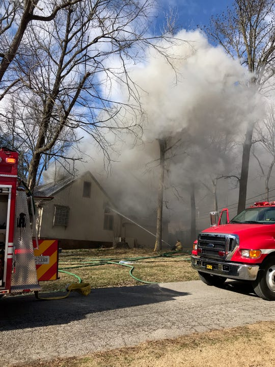 Firefighters work the scene at 3232 Tanglewood Drive Monday.