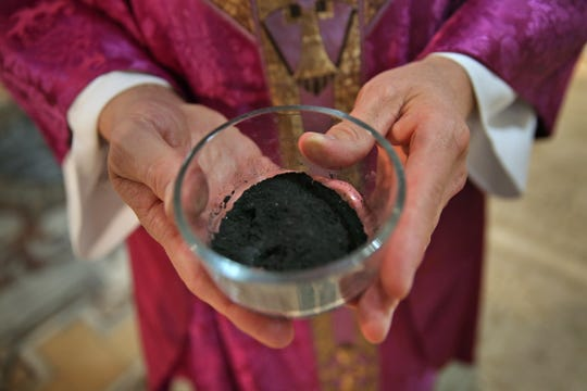 Father Rick Nagel shows the ashes used during Ash Wednesday service at Saint John Catholic Church, Wednesday, February 10, 2016.