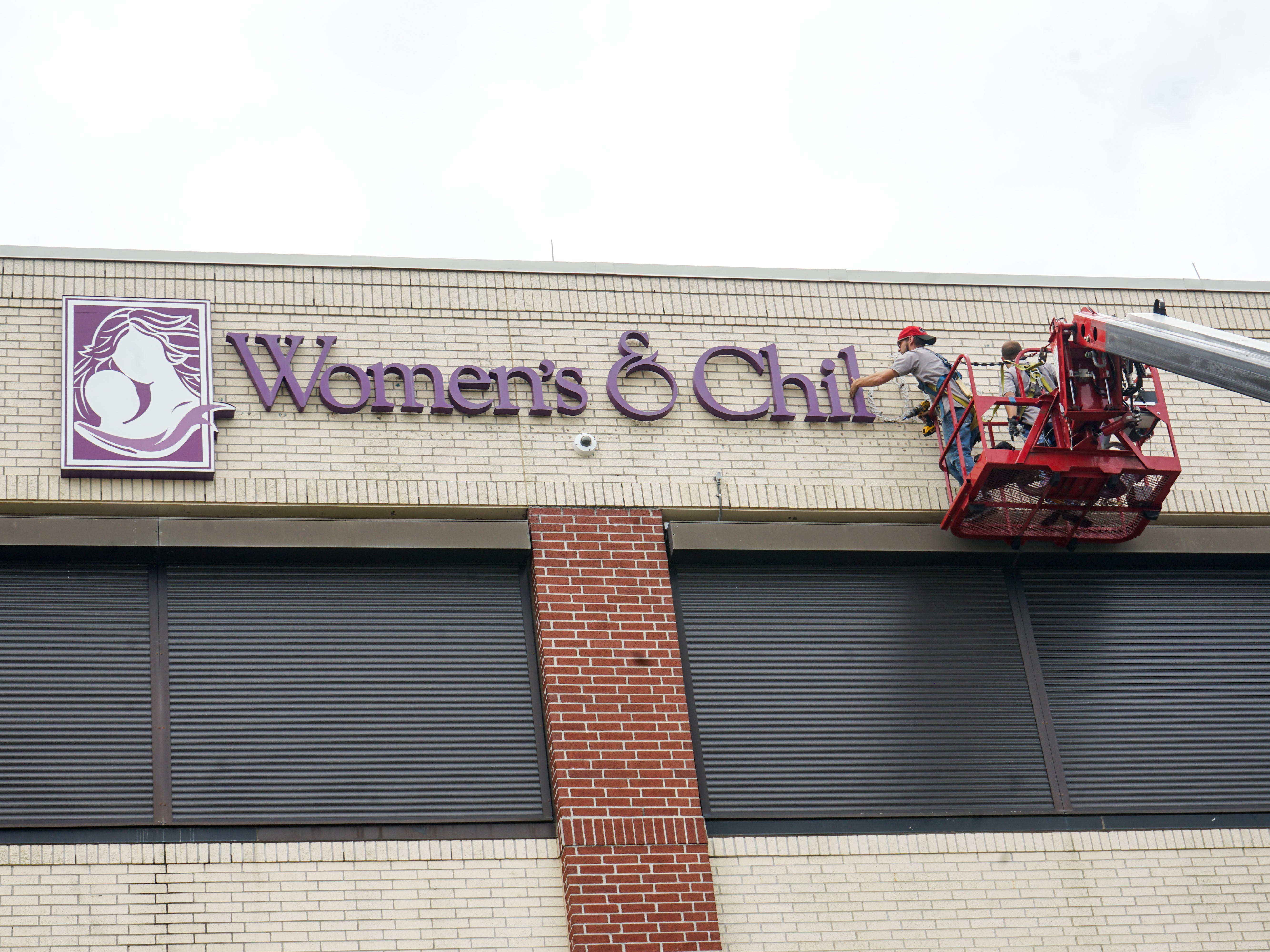 Crews remove the former sign from the front of Our Lady of Lourdes Women's & Children's Hospital in Friday, March 1. The new hospital sign is scheduled to be up in coming days.
