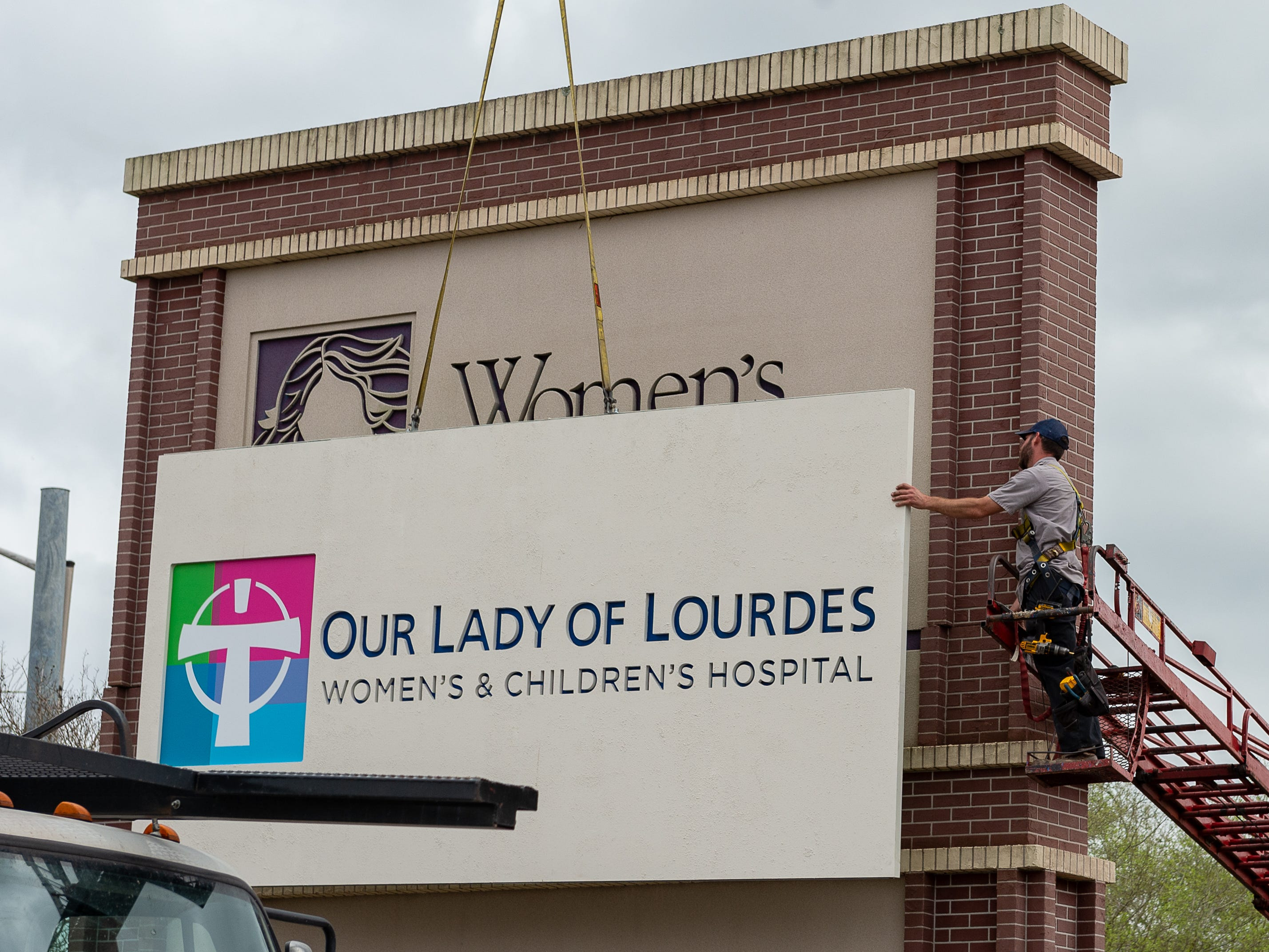 Crews replace the monument sign at the Ambassador Caffery Parkway main entrance to the Our Lady of Lourdes Women's & Children's Hospital grounds on Friday, March 1.