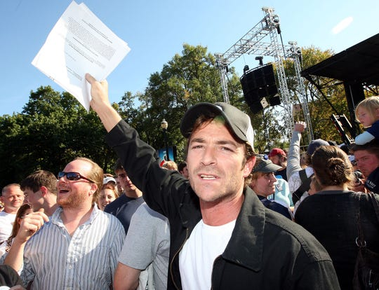 Actor Luke Perry holds a voter registration form in the air before a Bruce Springsteen concert on Sunday, Oct. 5, 2008, on the campus of Ohio State University, in Columbus, Ohio. Perry was encouraging Barack Obama supporters to register and take advantage of Ohio's early voting period. (AP Photo/Terry Gilliam)