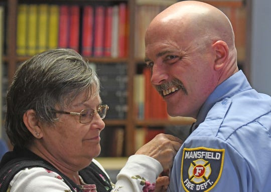 Roann Lucas, mother of Joe Lucas, pins a Captain's badge on him during a promotion and swearing-in ceremony at the Third Street station Monday morning.
