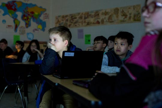 Joel Madden, 12, and other students watch a video during Jessica Washington's sixth-grade science class at Lakeland Middle Preparatory School. Every student at Lakeland Middle Preparatory School has a Chromebook laptop that they use instead of textbooks.