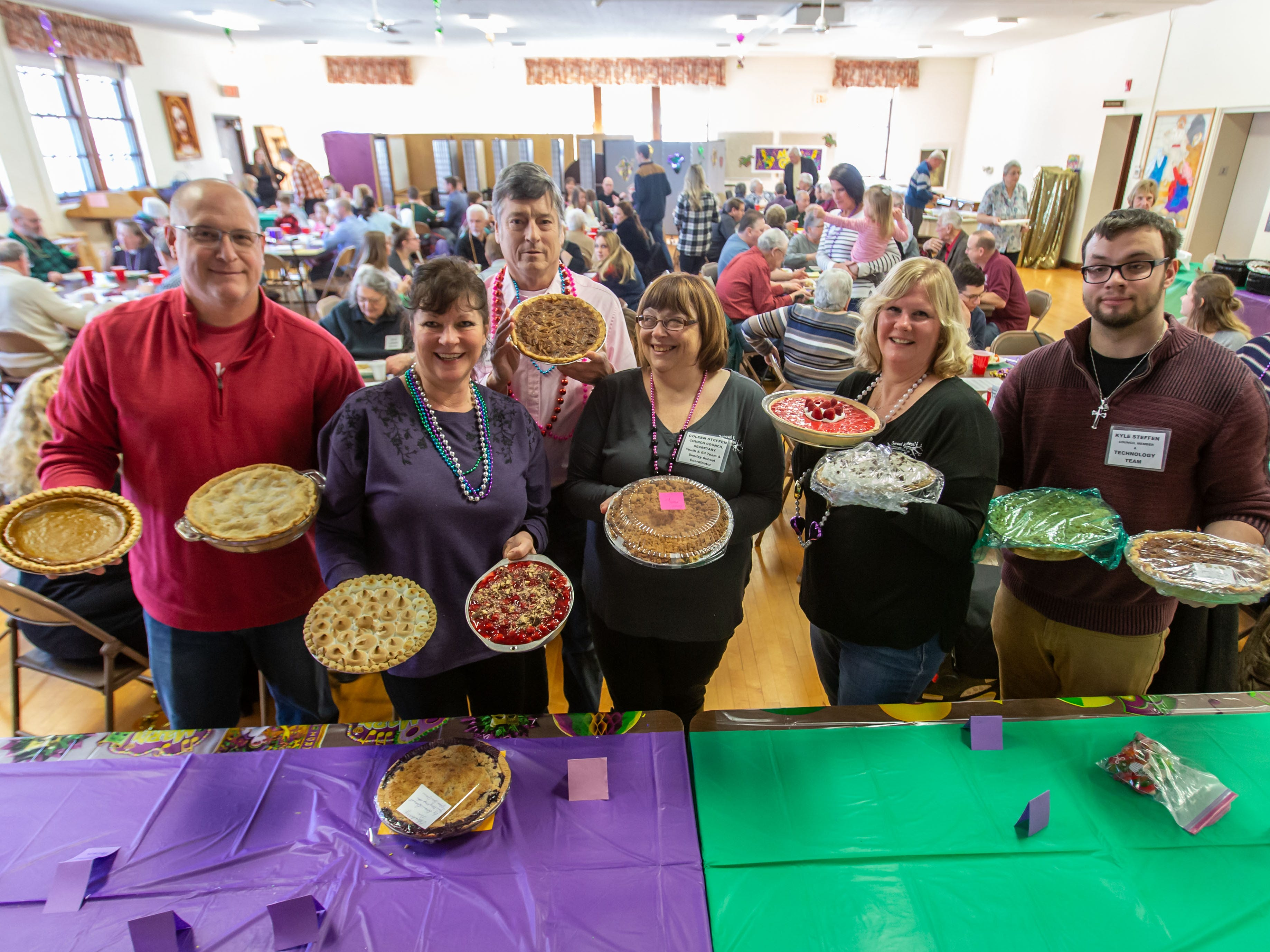 Parishioners (from left) Mike Wendorf, Debbie Wolff, Ray Jacques, Coleen Steffen, Holly Hupfer and Kyle Steffen display a few of the home-baked pies up for auction during the Mardi Gras Pig Roast and pie auction at Immanuel Lutheran Church in Cedarburg on Sunday, March 3, 2019. The event is a fundraiser for the church.