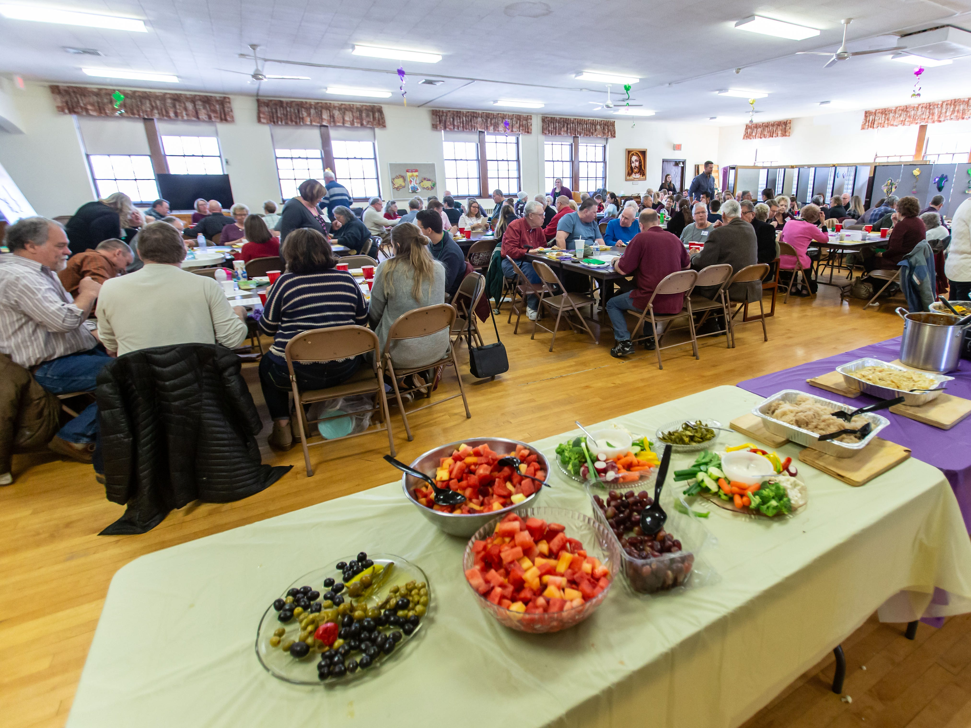 Parishioners and guests enjoy a delicious feast during the Mardi Gras Pig Roast and pie auction at Immanuel Lutheran Church in Cedarburg on Sunday, March 3, 2019. The event is a fundraiser for the church.