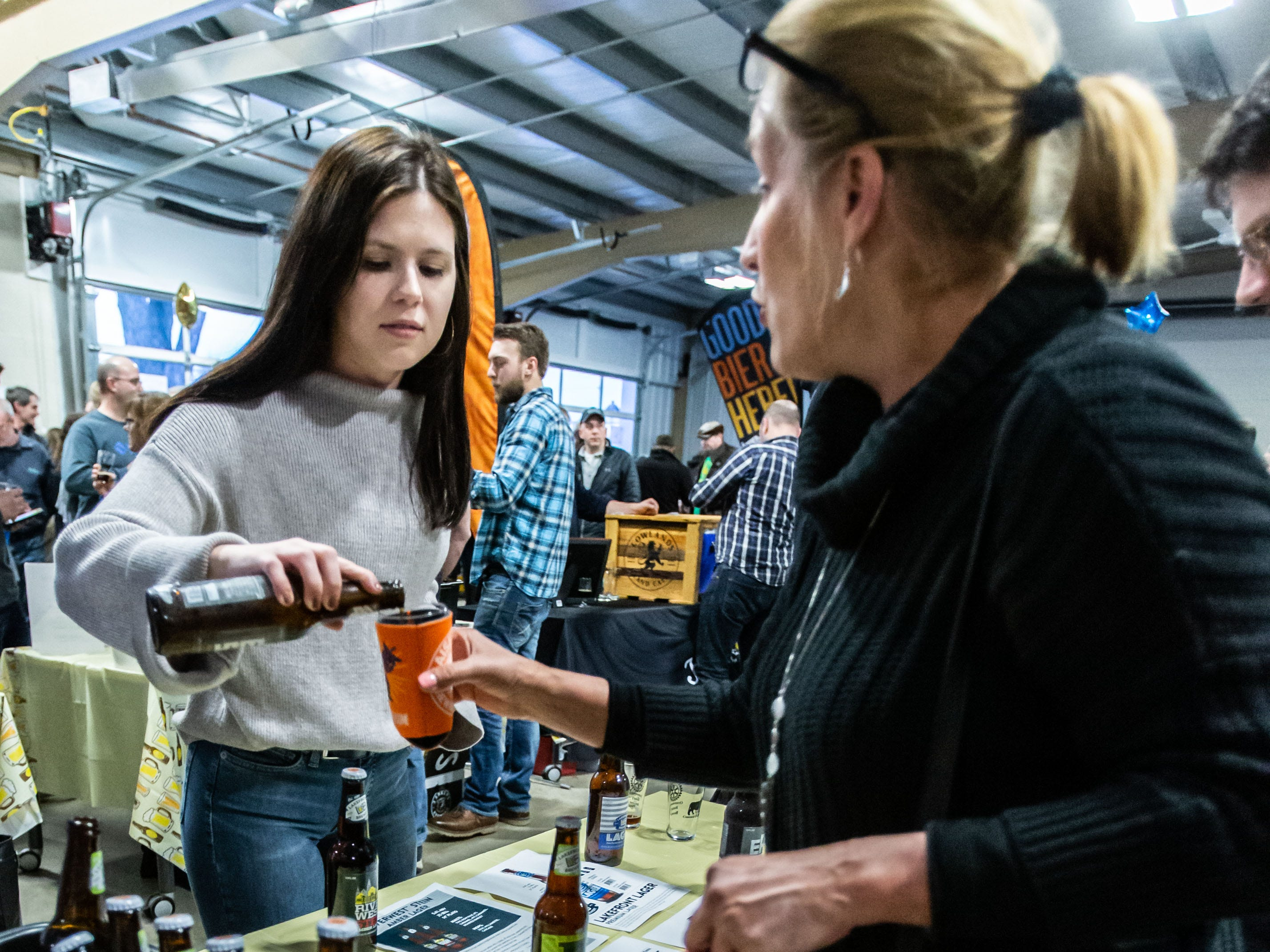 Meghan Hoerl of Lakefront Brewery pours a beer for Stacey Cibulka of Ixonia during the Oconomowoc Rotary Club's 13th annual Oconomowoc Wine & Brewfest in Okauchee on Saturday, March 2, 2019.
