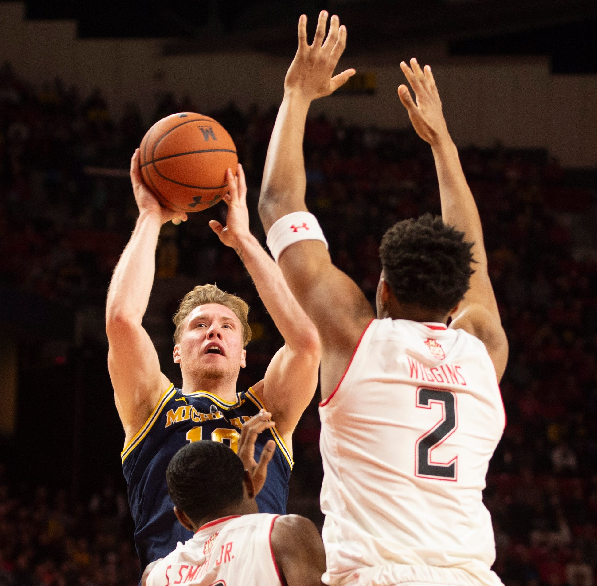 Michigan forward Ignas Brazdeikis shoots over Maryland defenders during the first half at XFINITY Center on Sunday.