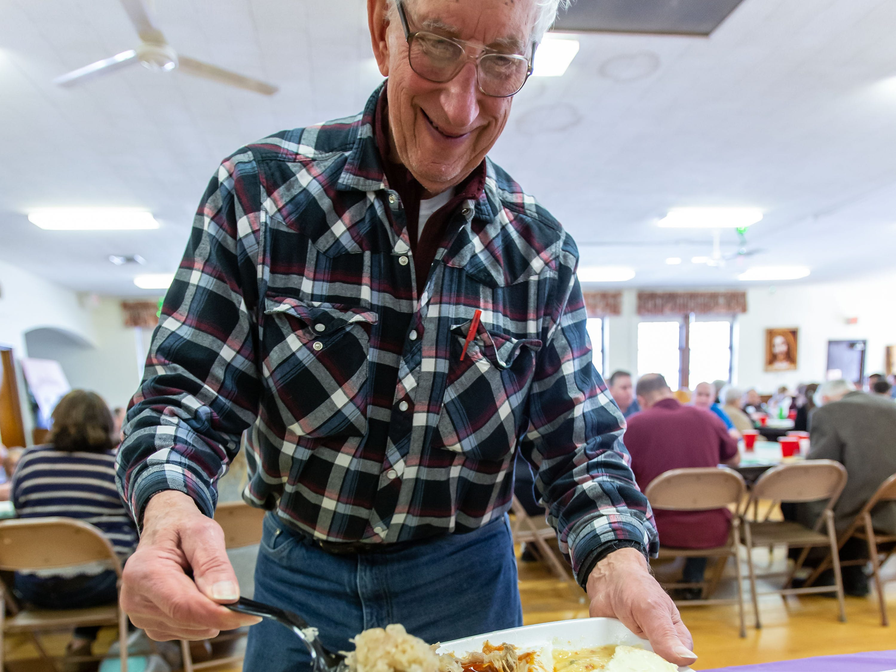 Roger Johnson of Cedarburg fills a plate during the Mardi Gras Pig Roast and pie auction at Immanuel Lutheran Church in Cedarburg on Sunday, March 3, 2019.