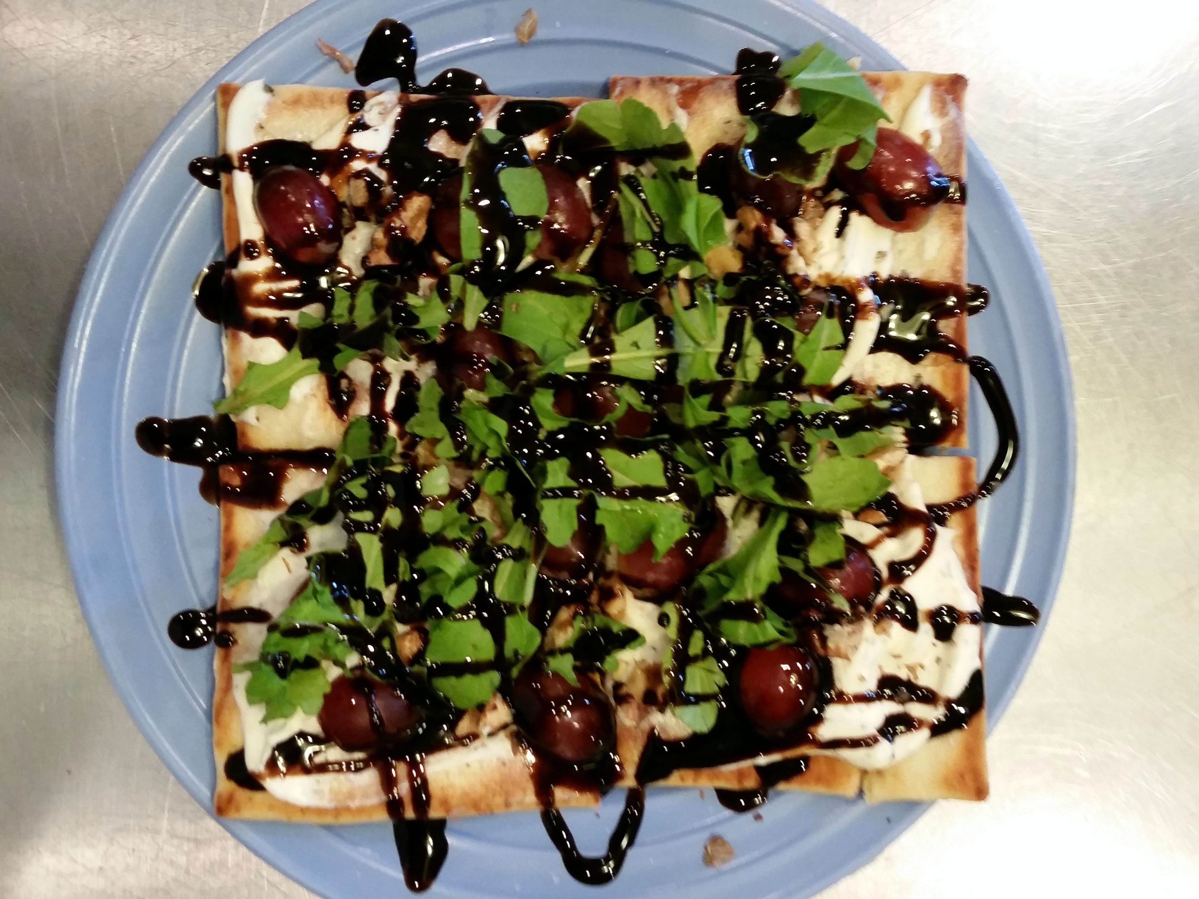 Red grape flatbread, topped with arugula and drizzled with a balsamic glaze, is a regular on the high tea menu.