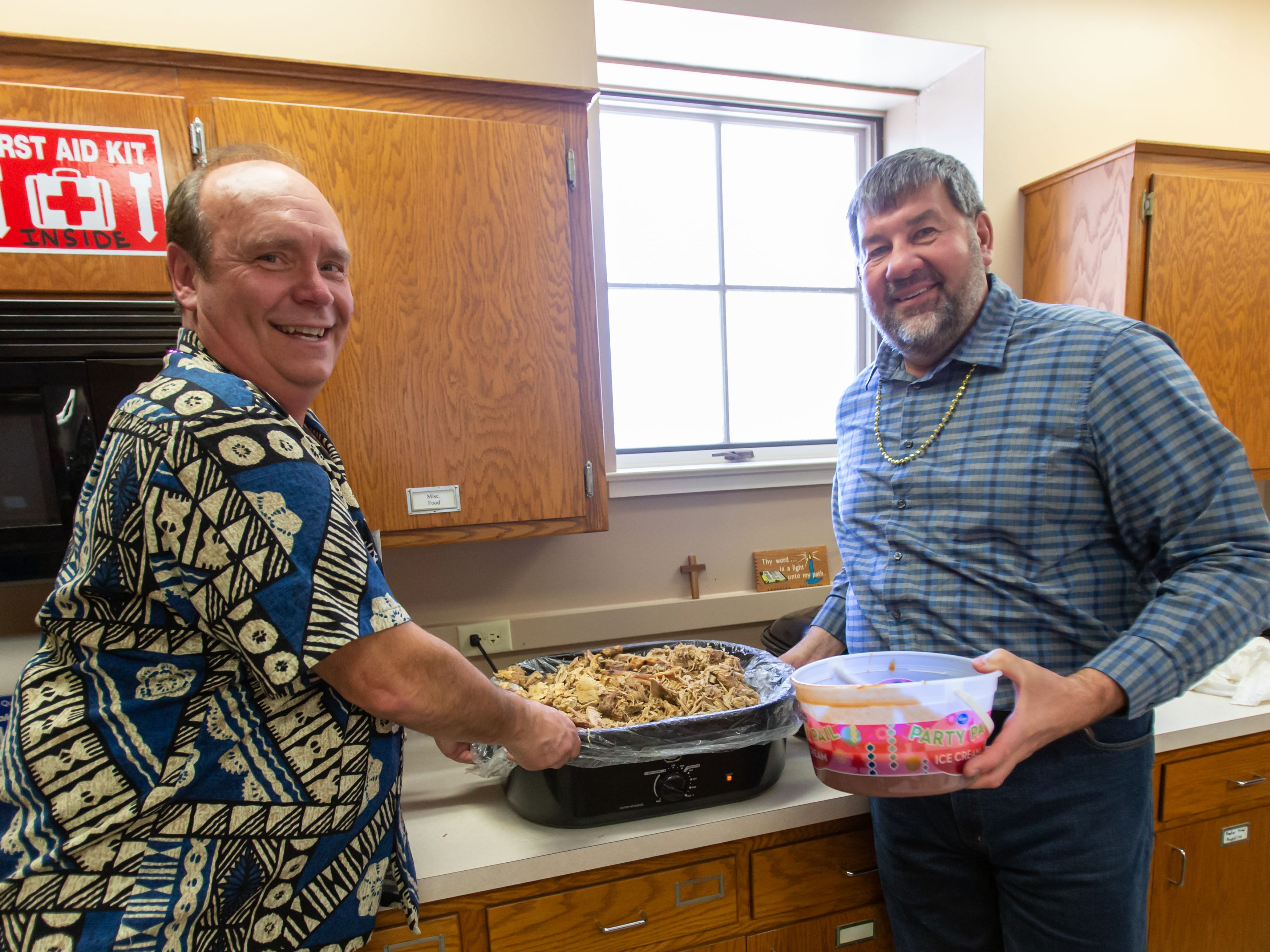 Mike Wolff and Eric Hackert of Cedarburg prepare a pot of shredded pork during the Mardi Gras Pig Roast and pie auction at Immanuel Lutheran Church in Cedarburg on Sunday, March 3, 2019.