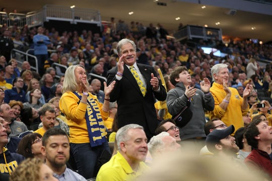 """Rick Smith (second from left) is up and out of his seat jumping and clapping as """"Jump Around"""" is played at the Marquette vs. Creighton basketball game at Fiserv Forum on Sunday. With him are his wife, Joan Smith, Wyatt Schick of Shorewood and Greg Renz of Fox Point. Rick Smith has joined the students for the jumping around tradition at home games the past 12 years."""