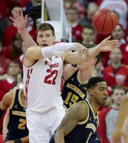 Wisconsin forward Ethan Happ  rifles a pass against Michigan in January.