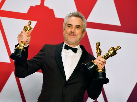 "Alfonso Cuaron poses with the awards for best director, best foreign-language film and best cinematography for ""Roma"" at the Oscars on Feb. 24. The success of ""Roma,"" distributed by Netflix, has triggered a debate among Hollywood's top players about the role of streaming movies at the Oscars."