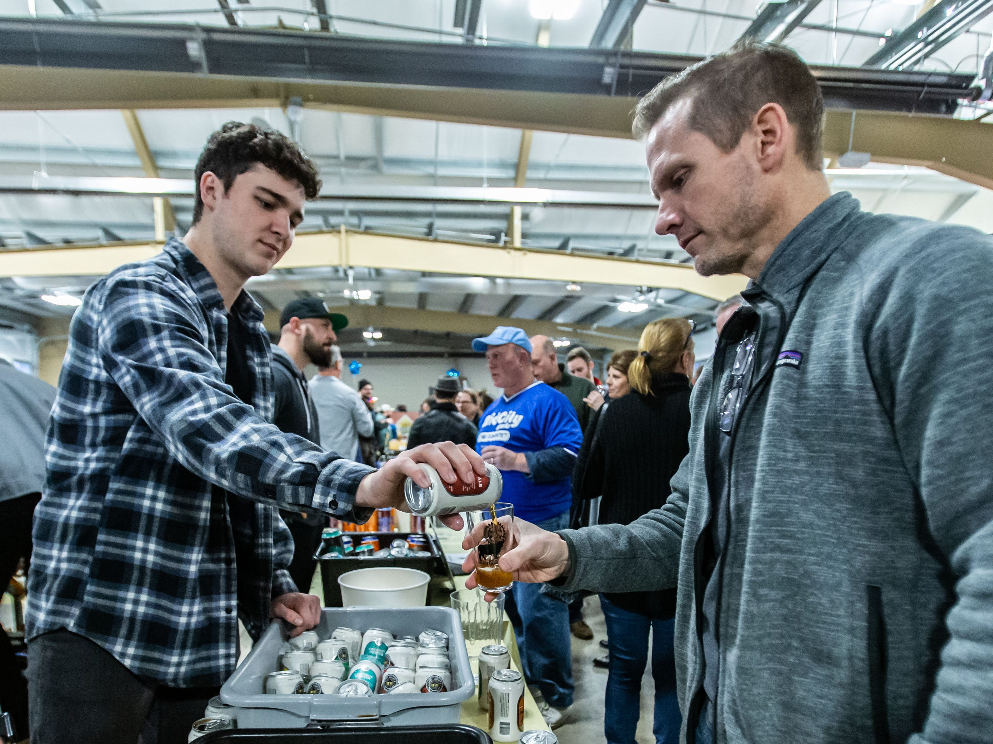 Dan Zurawski of City Lights Brewing Company pours a beer for Brian Wargula of Nashotah during the Oconomowoc Rotary Club's 13th annual Oconomowoc Wine & Brewfest in Okauchee on Saturday, March 2, 2019.