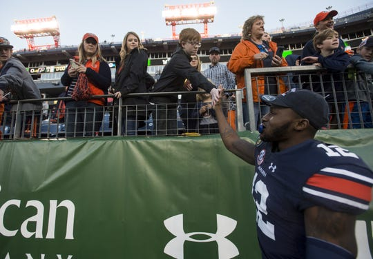 Auburn defensive back Jamel Dean (12) high fives fans after the Music City Bowl at Nissan Stadium in Nashville, Tenn., on Friday, Dec. 28, 2018. Auburn defeated Purdue 63-14.
