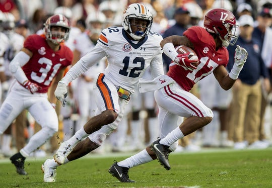 Alabama wide receiver Jaylen Waddle (17) tries to escape Auburn defensive back Jamel Dean (12) in first half action during the Iron Bowl at Bryant-Denny Stadium in Tuscaloosa, Ala., on Saturday November 24, 2018.