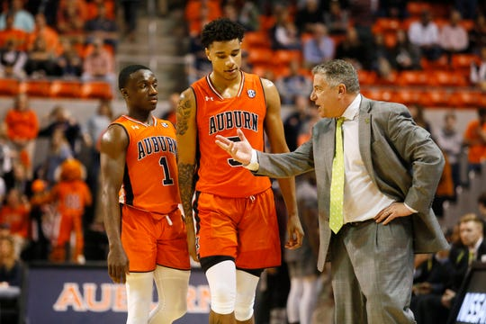 Auburn coach Bruce Pearl speaks with forward Chuma Okeke (5) and guard Jared Harper (1) during the second half against Mississippi State on March 2, 2019.