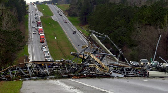 A fallen cell tower lies across U.S. Route 280 highway in Lee County, Ala., in the Smiths Station community after what appeared to be a tornado struck in the area Sunday, March 3, 2019. Severe storms destroyed mobile homes, snapped trees and left a trail of destruction amid weather warnings extending into Georgia, Florida and South Carolina, authorities said. (Mike Haskey/Ledger-Enquirer via AP)