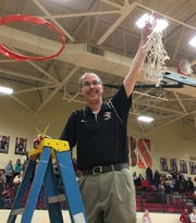 Cheatham County coach Jim Gibbs holds up the net to celebrate the Lady Cubs' win over Creek Wood.