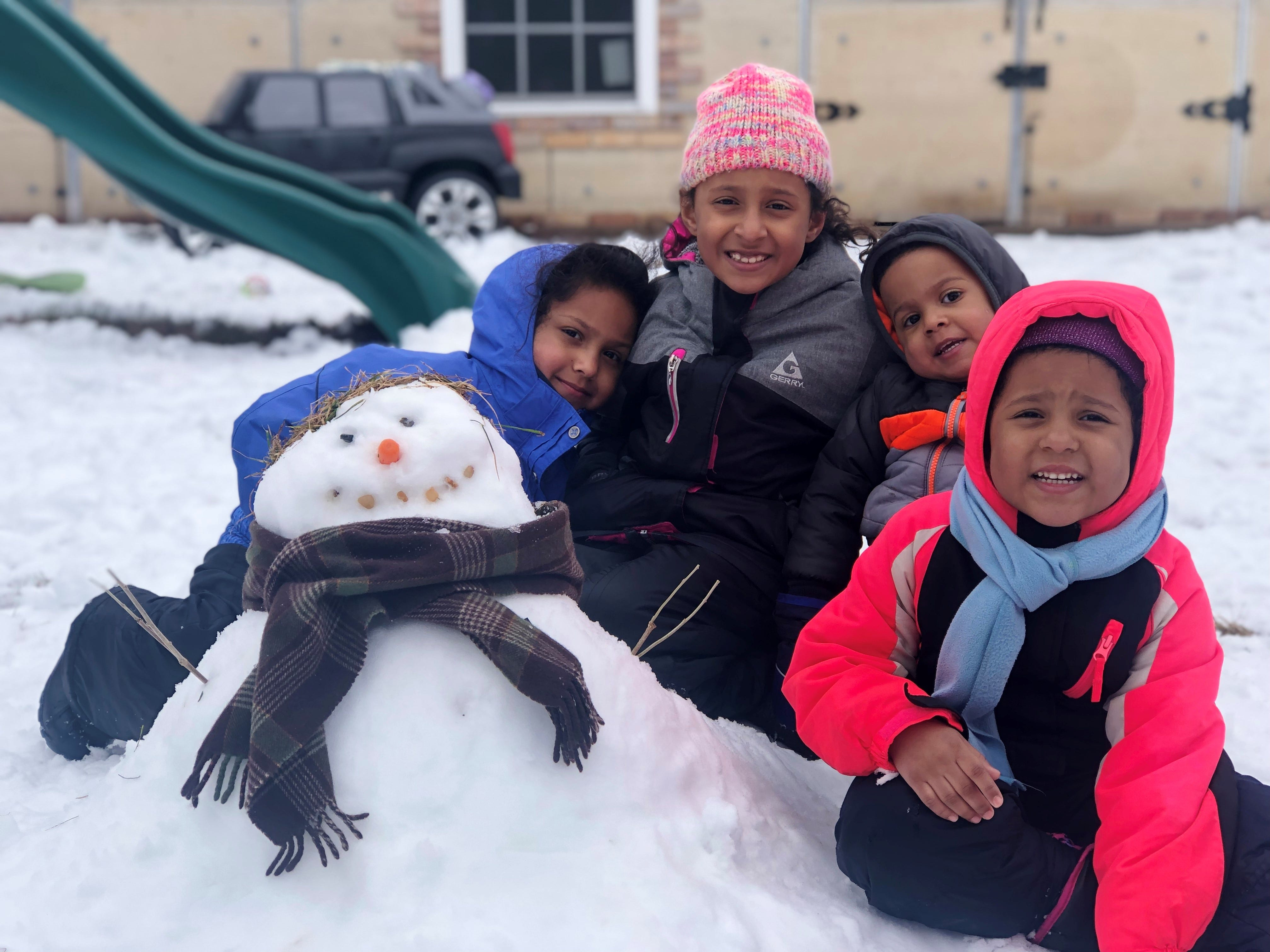 Nutley's Abutaah family - Ameera, 6, Sophia, 8, Lydia, 4, and Omar, 2 - pose with their snowman on Monday.