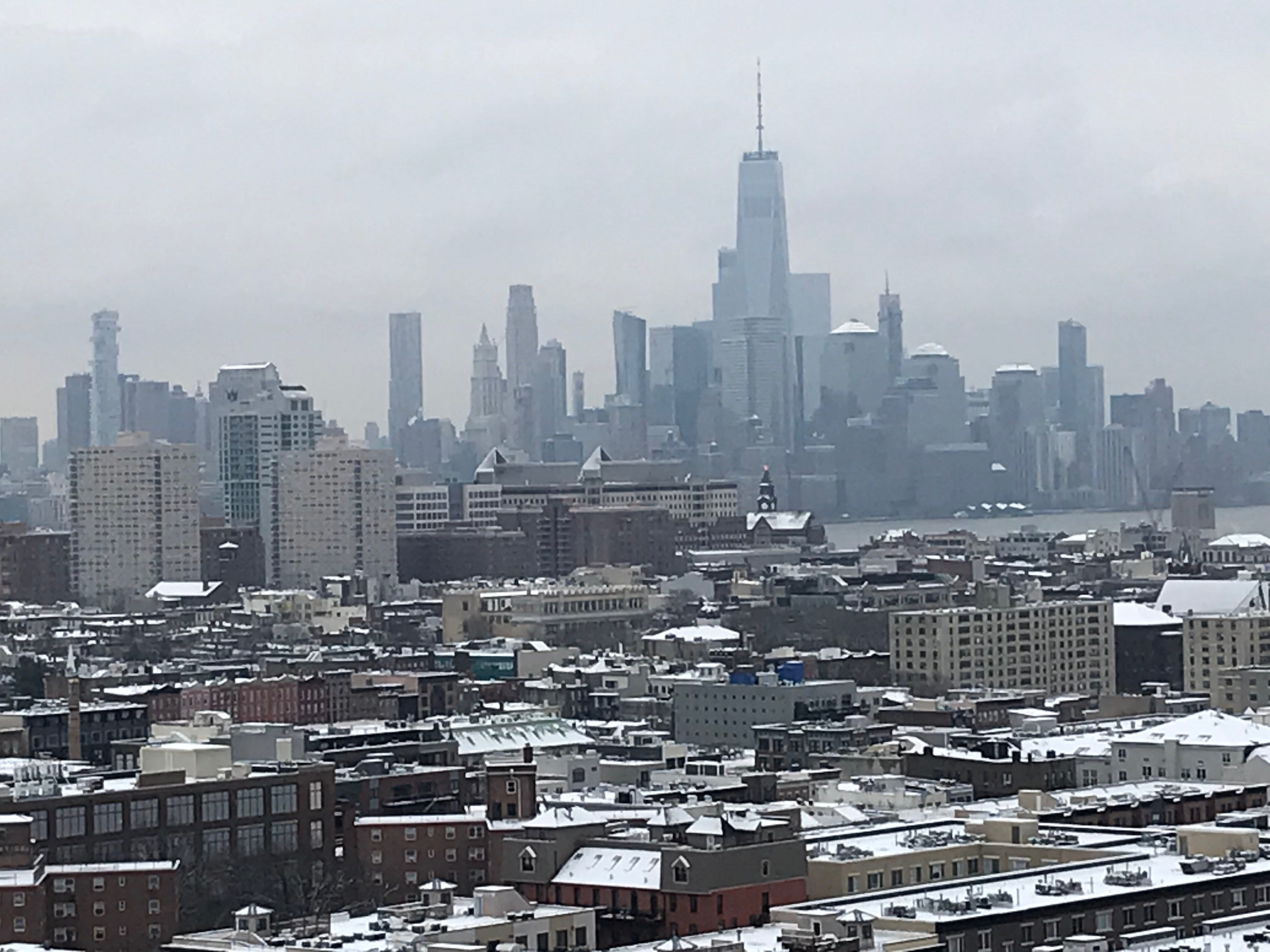 Dawn breaks on a snow-capped North Jersey with the World Trade Center and the lower Manhattan skyline in the background.