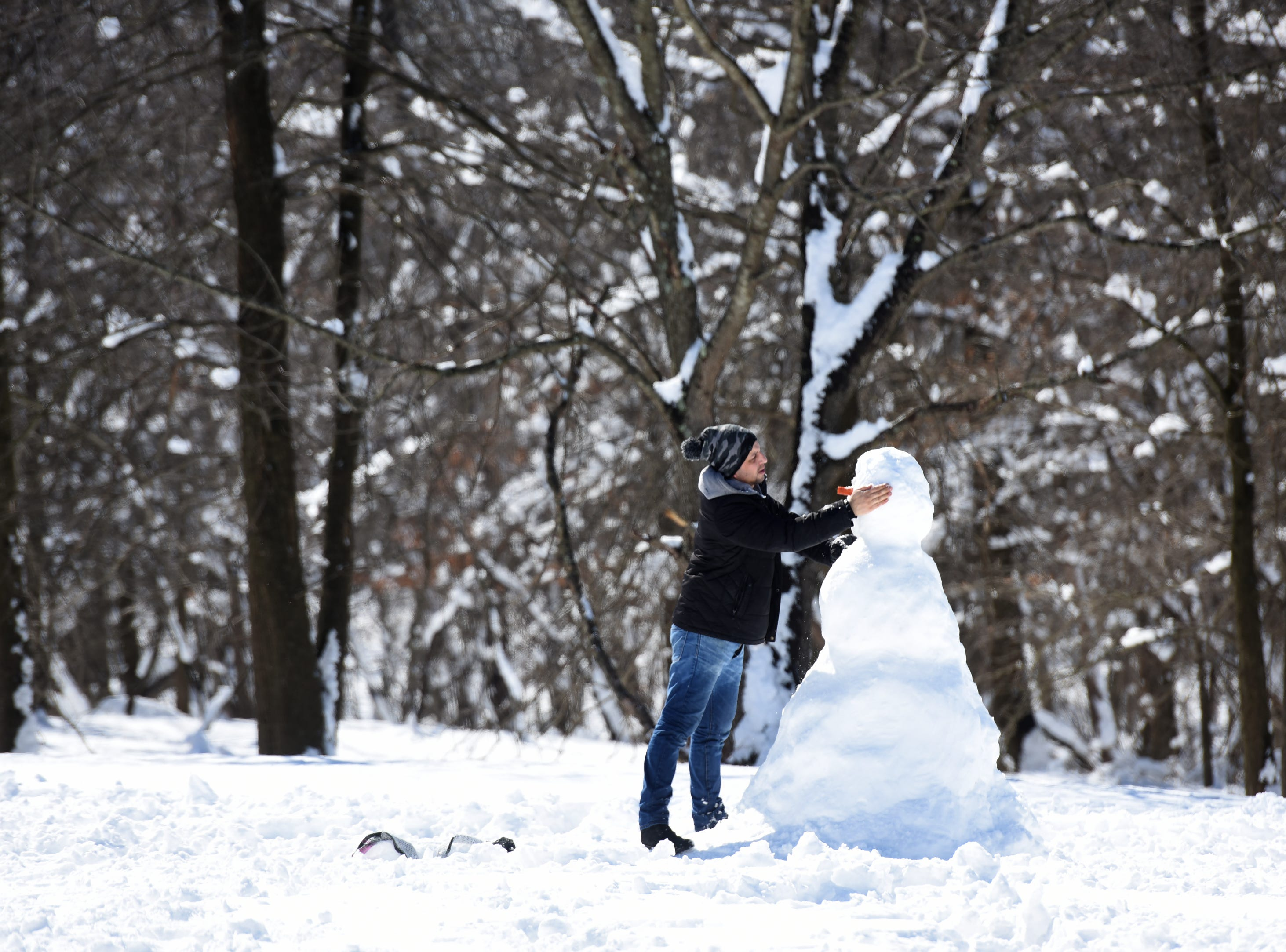 Mohamed Aijyyousi of Clifton, makes a snowman for his kids at Garret Mountain Reservation on Monday, March 4, 2019.