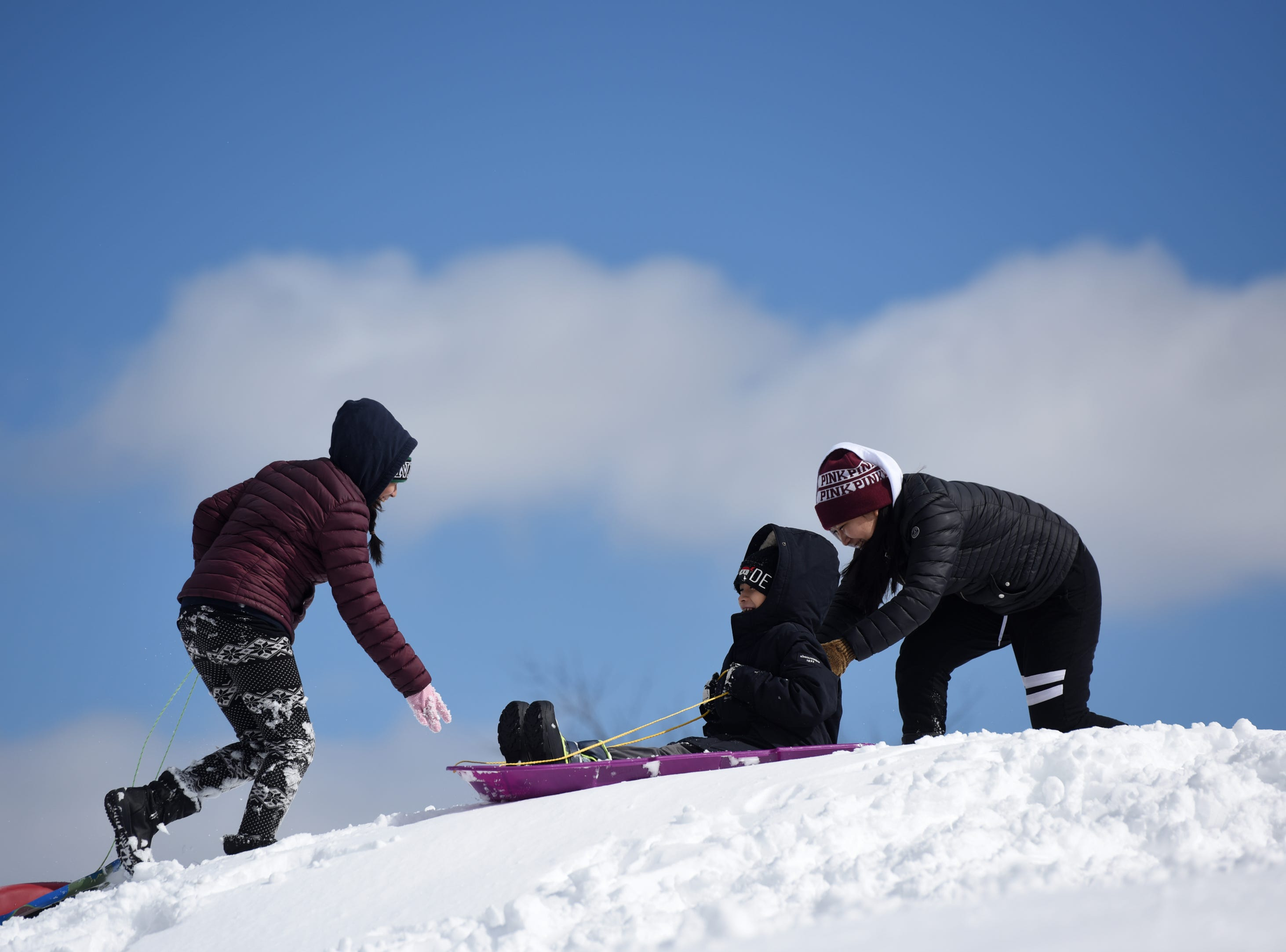 Sisters Brianna Cruz, 11 and Giselle Cruz 14, from left, give their brother Brandon Cruz, 9, a push while sledding at Garret Mountain Reservation on Monday, March 4, 2019.