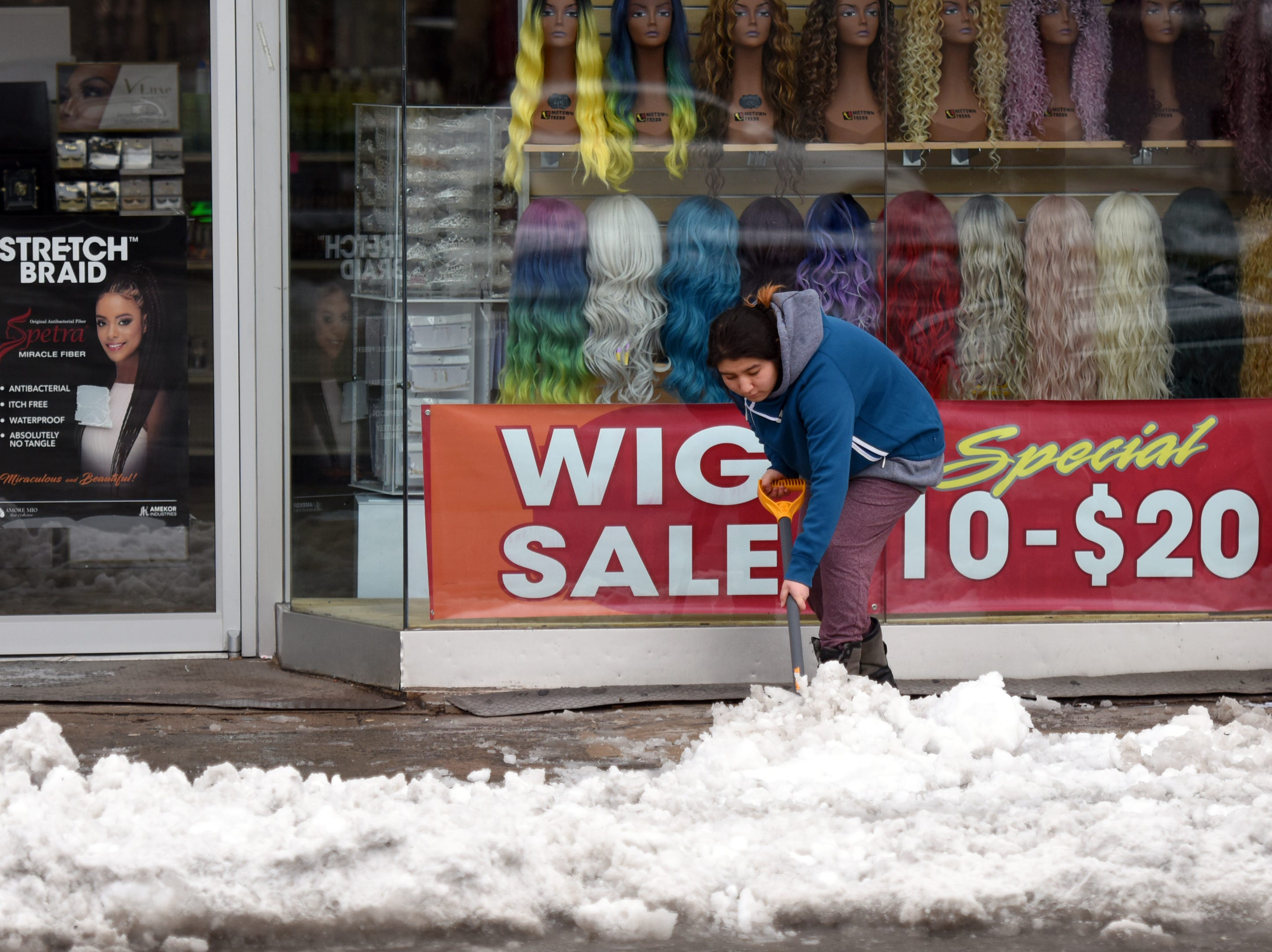 A woman clear snow from the sidewalk in front of a business on Main Ave. in Passaic on Monday, March 4, 2019.
