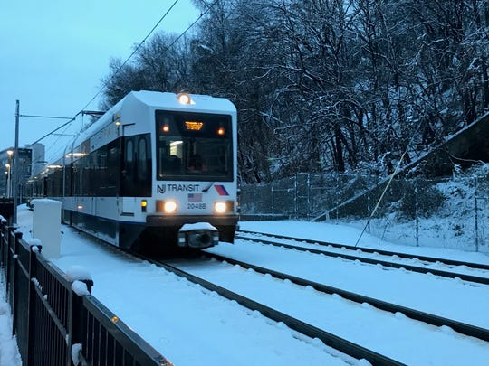 Light rail train over snowy tracks in Hoboken.