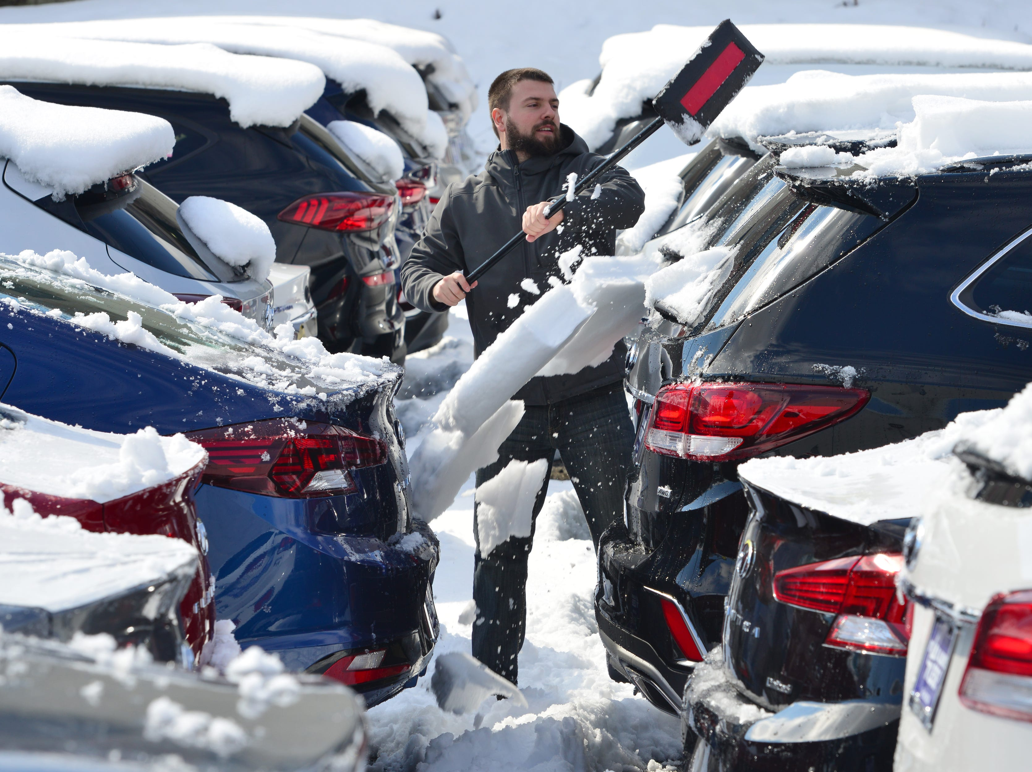 Nuno Santos clears the snow from new cars for sale at the Hyundai dealership on Route 4 in Paramus on Monday March 4, 2019.