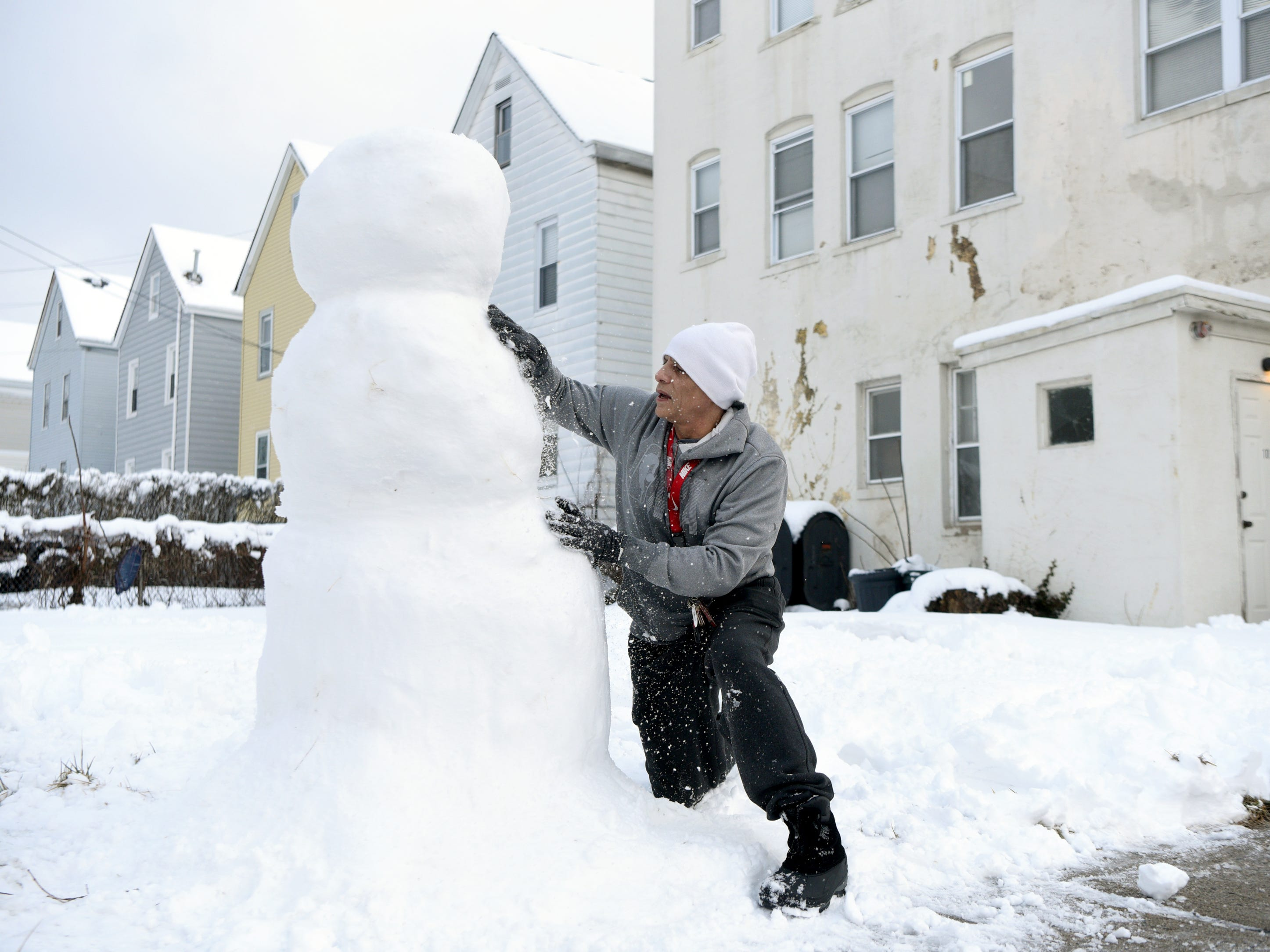 Michael Rivera builds a snowman on the lawn of his Elm St. home for his daughters before they wake up on Monday, March 4, 2019.
