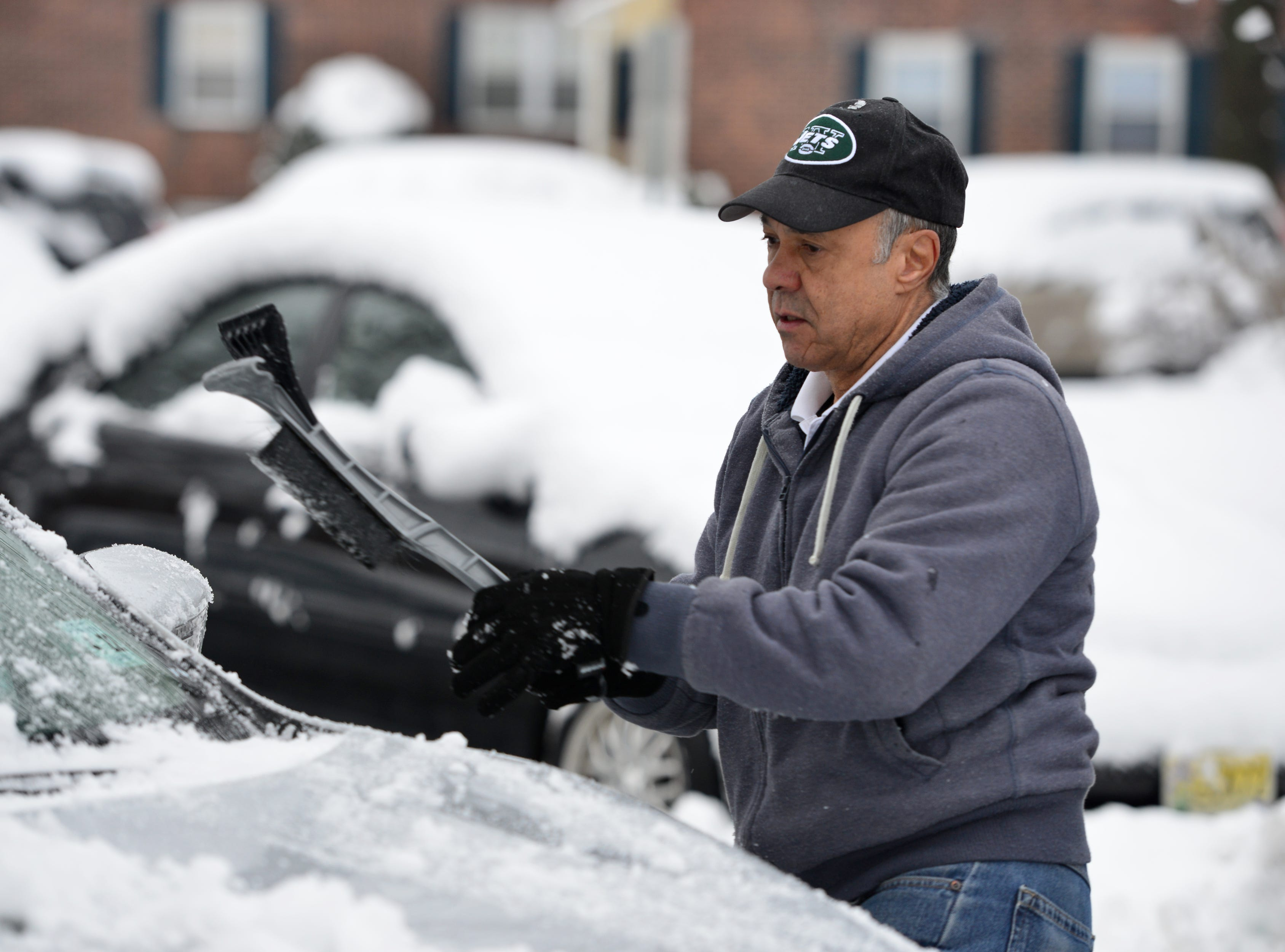 Francisco Paulino, of North Arlington, clears his car from snow in front of his home in North Arlington on Monday morning March 4, 2019.