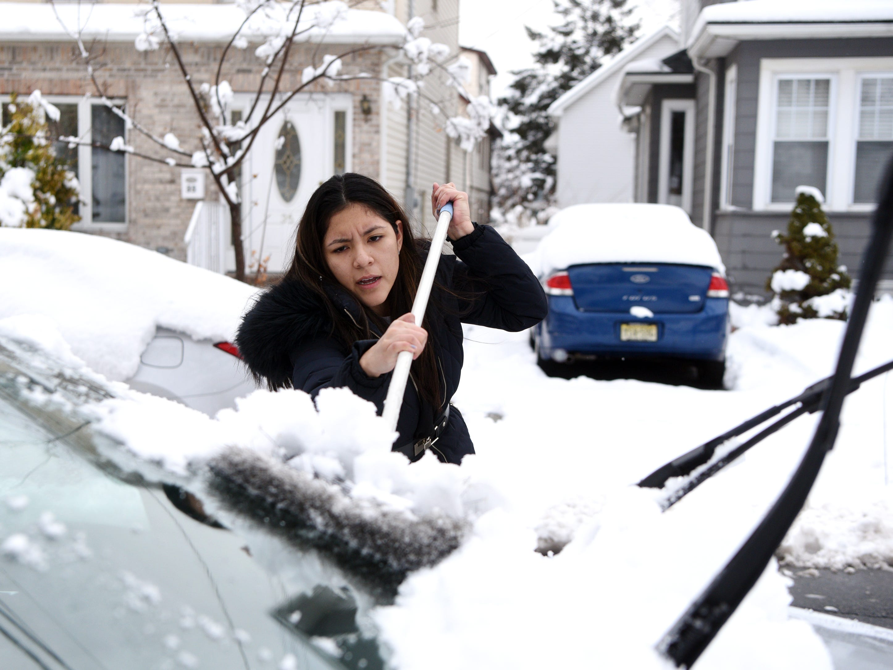 Gia Tapia clears snow from her car on Ward St. in Clifton so she can get to work on Monday, March 4, 2019.