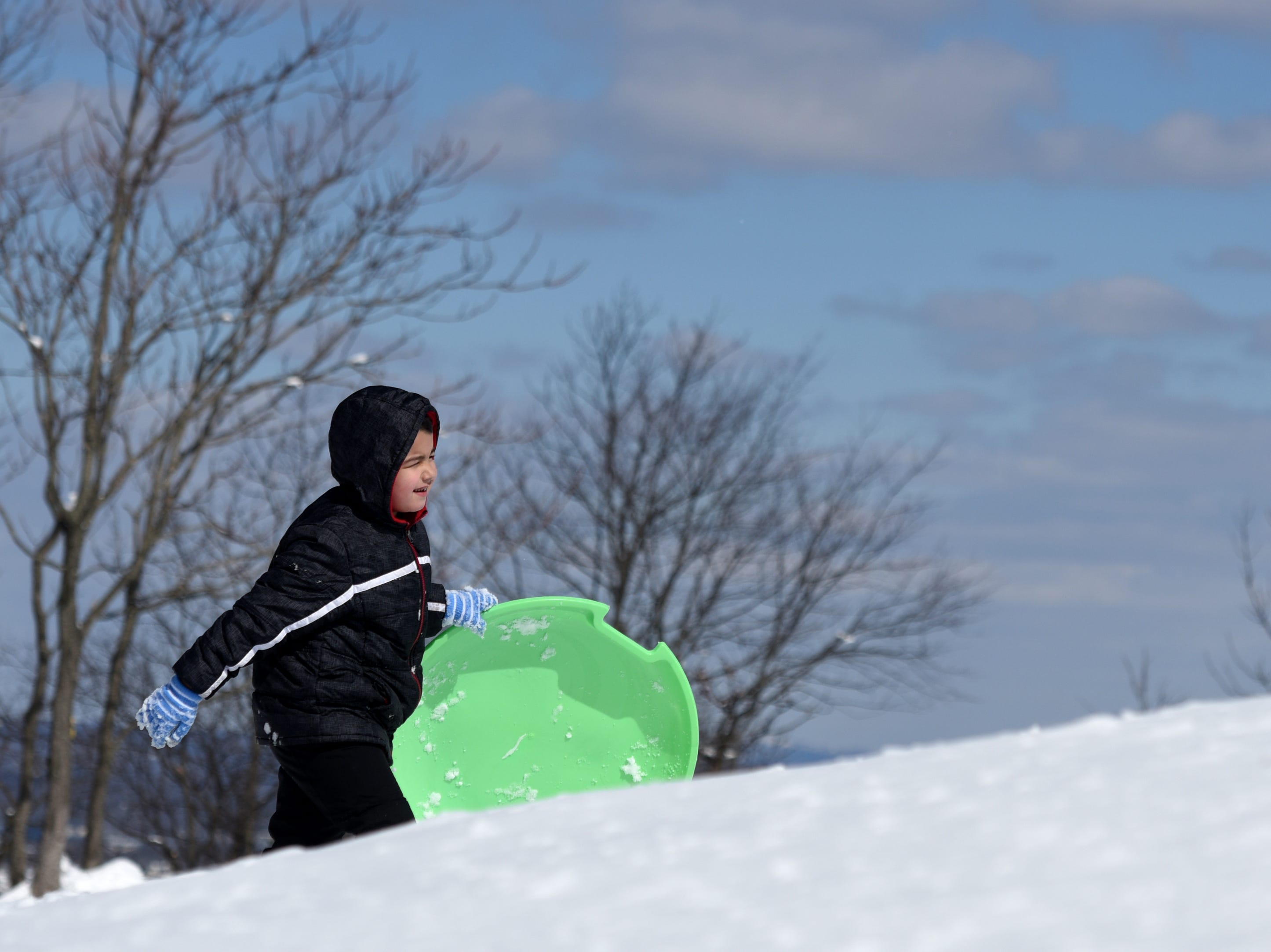 Elbi Gashi, 6, treks back up the hill while sledding at Garret Mountain Reservation on Monday, March 4, 2019.