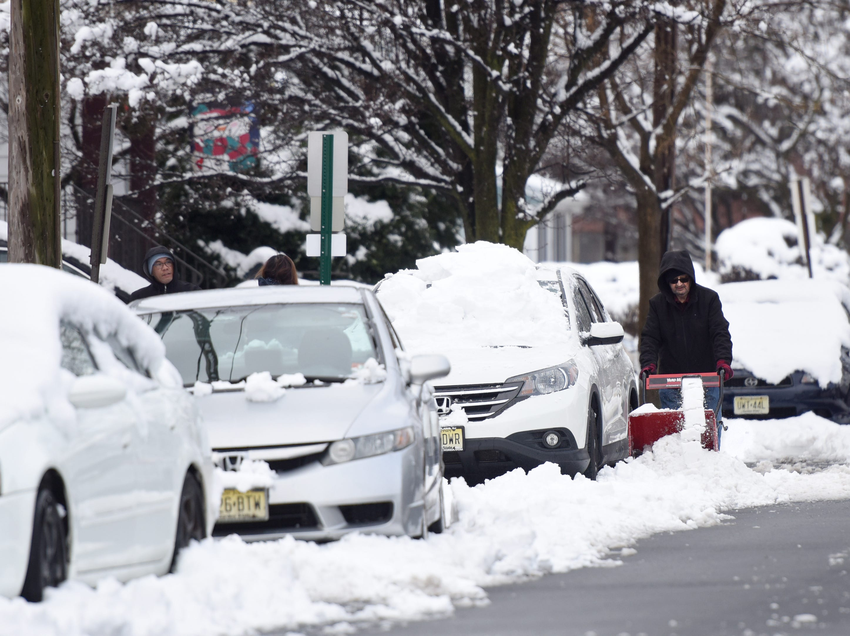 Residents on DeMott Ave. in Clifton clear snow on Monday, March 4, 2019.