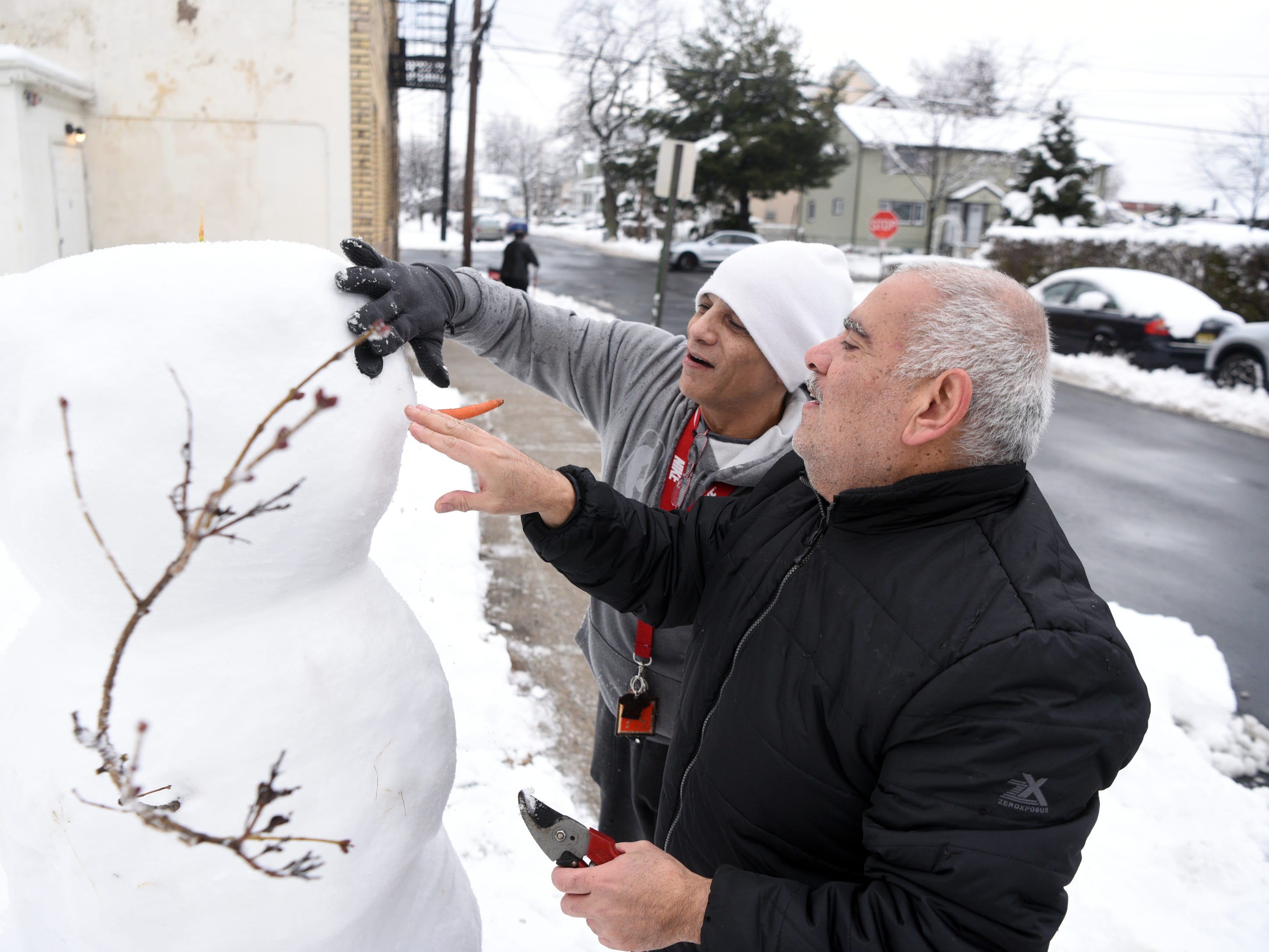 Michael Rivera and Max Melara place eyes in snowman Rivera built for his daughters before they wake up on Monday, March 4, 2019 in Clifton.