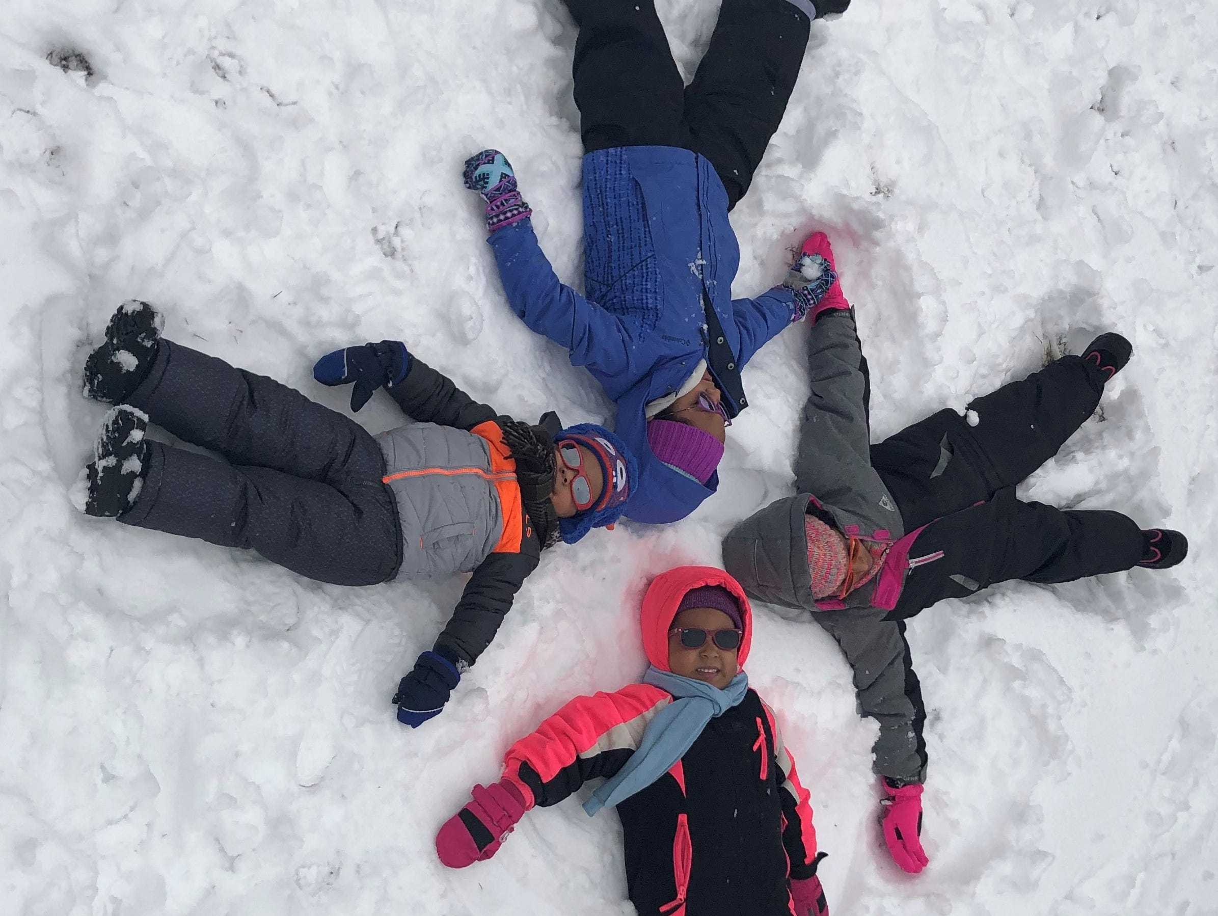 Nutley's Abutaah family - Ameera, 6, Sophia, 8, Lydia, 4, and Omar, 2, make angels in the snow on Monday.