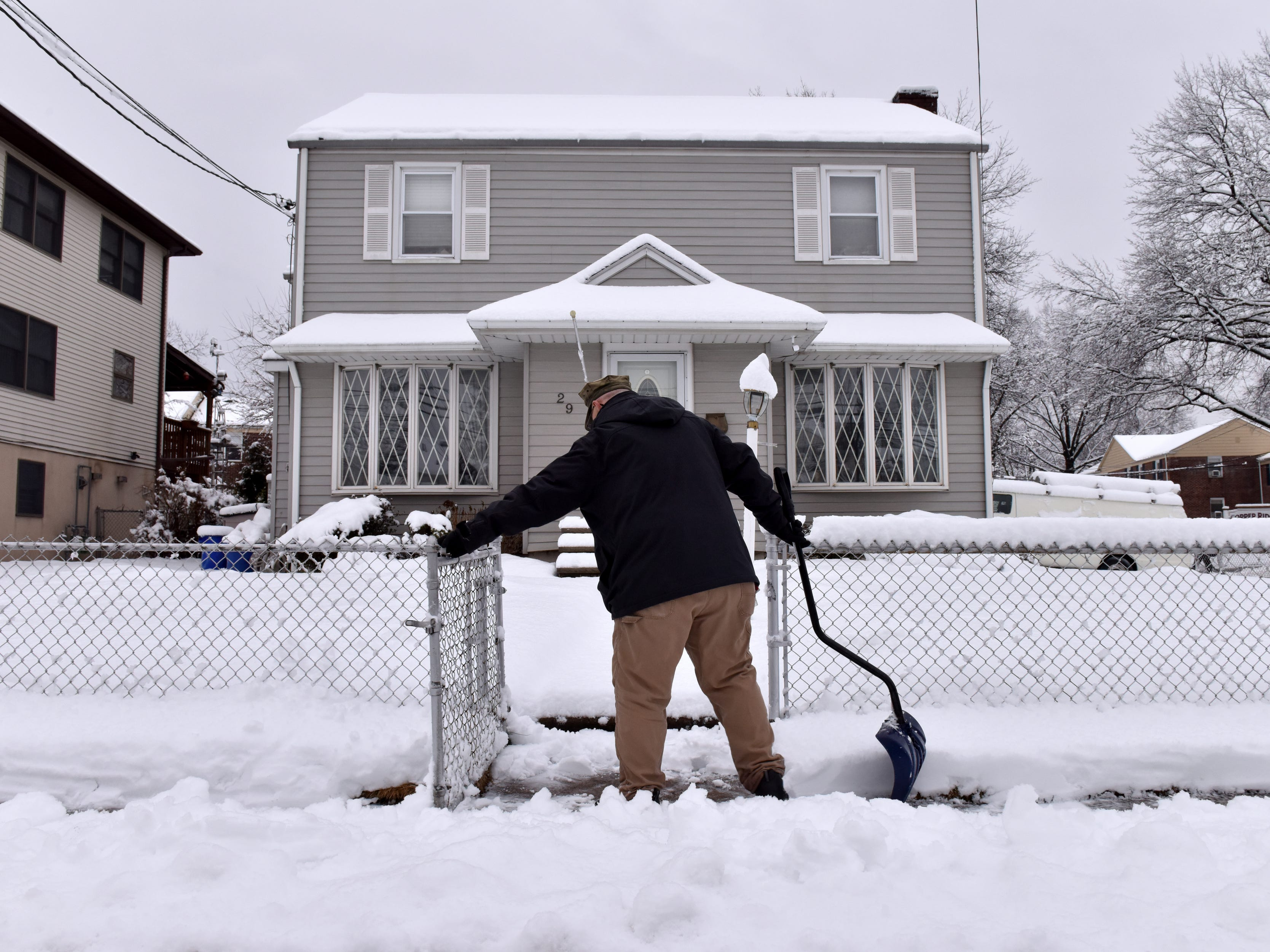 Bob Wilson clears the sidewalk in front of his home in North Arlington on Monday morning March 4, 2019.