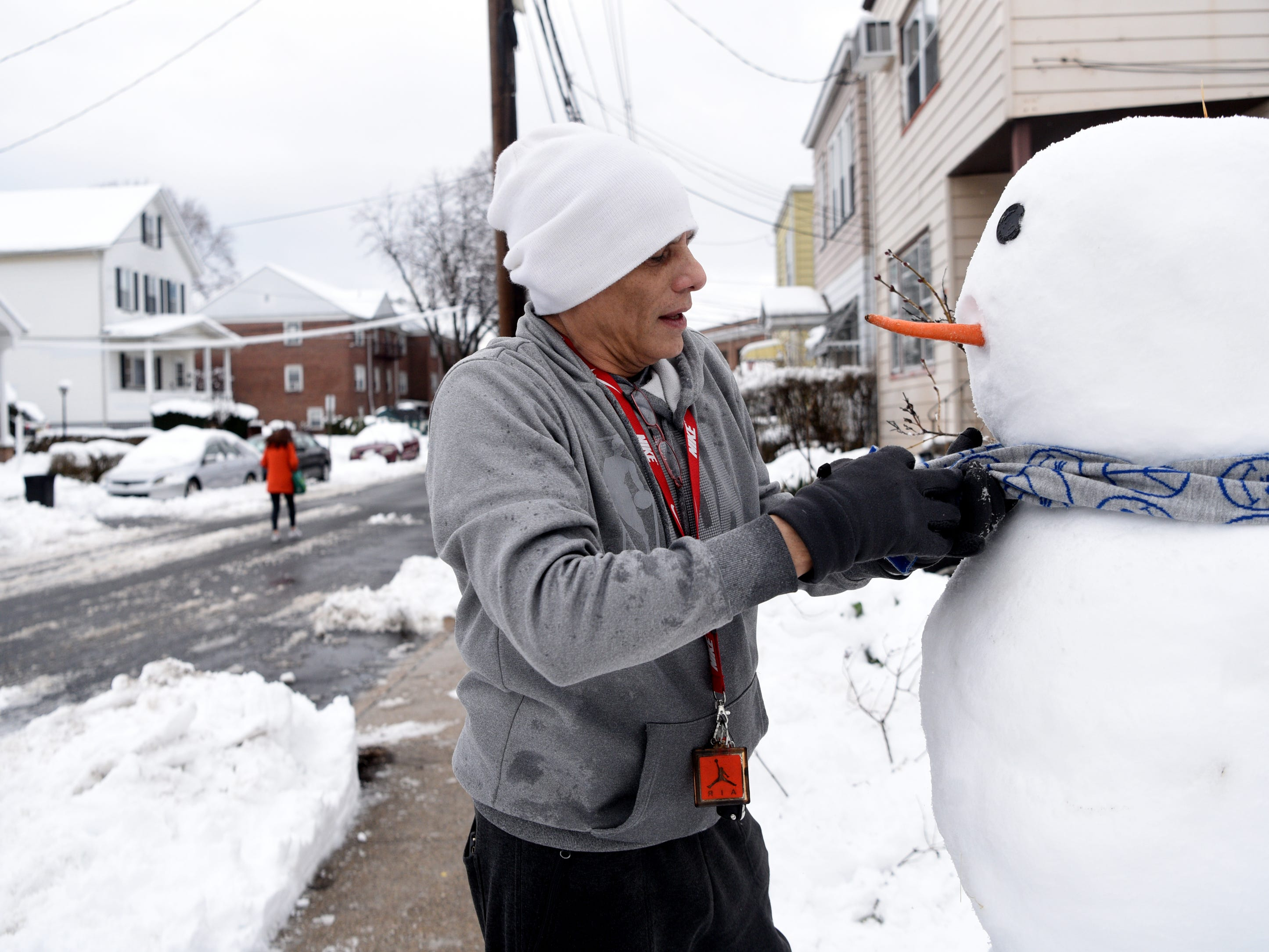 """Michael Rivera gives his """"Frosty,"""" the snowman a scarf in Clifton on Monday, March 4, 2019. Rivera promised to build a snowman for his daughters."""